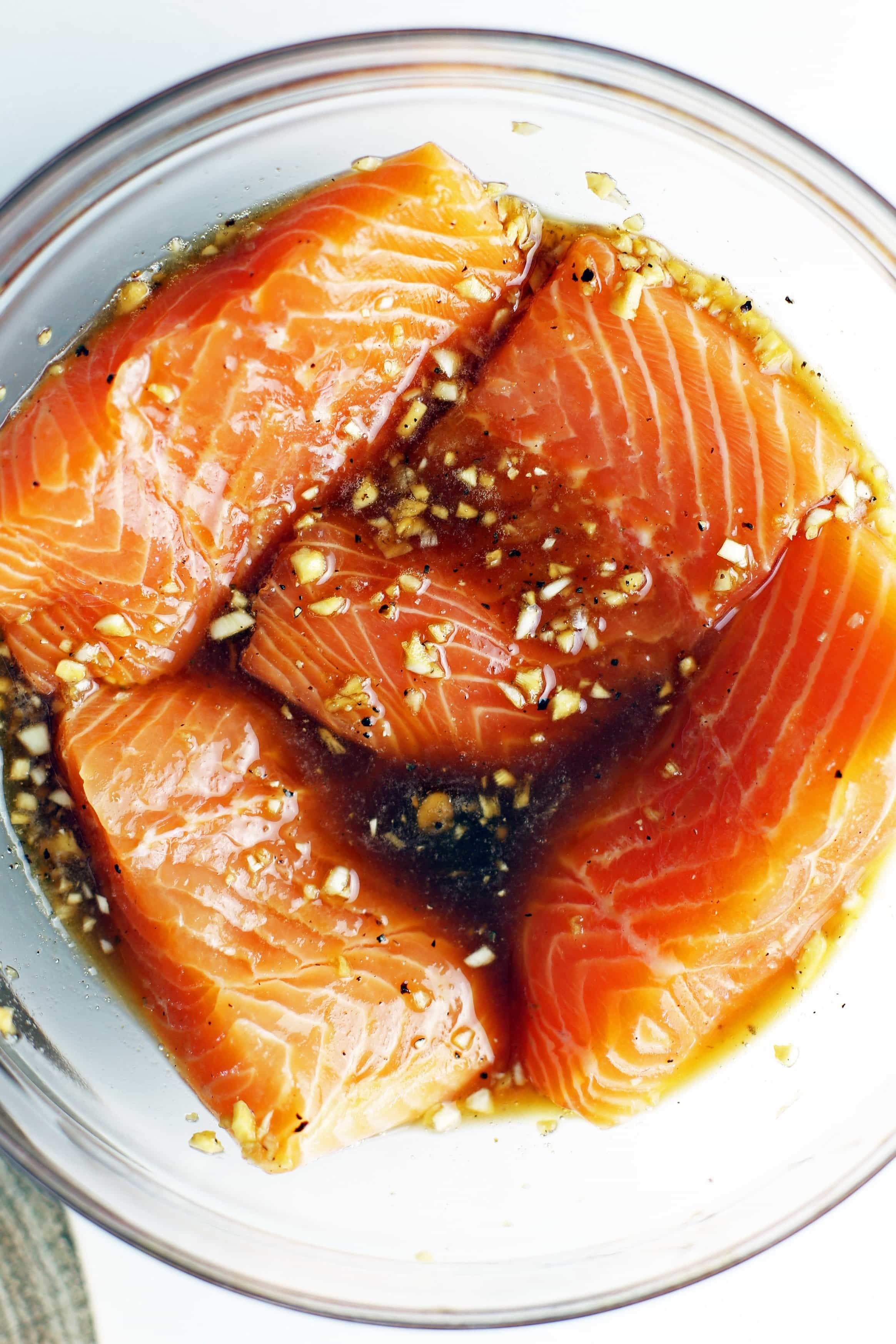 Four skinless salmon fillets covered in honey garlic marinade in a large glass bowl.