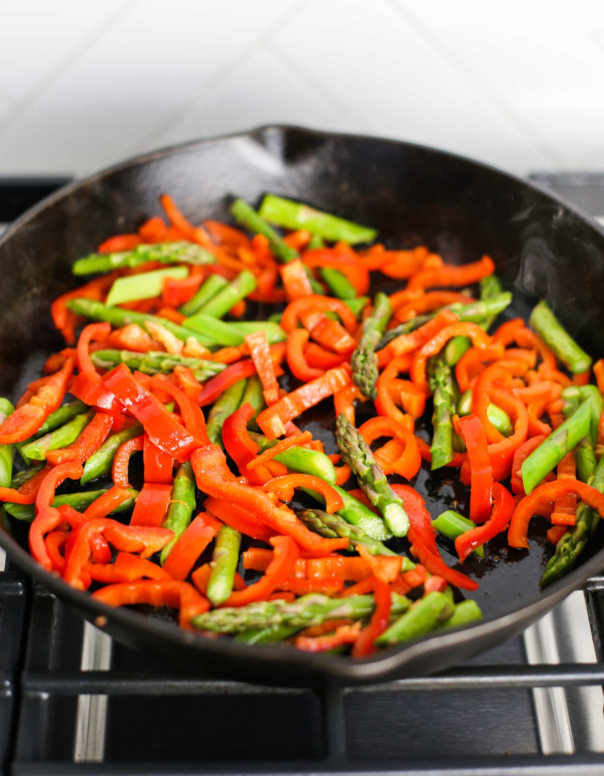 Sautéed chopped asparagus and red bell pepper in a cast iron skillet.