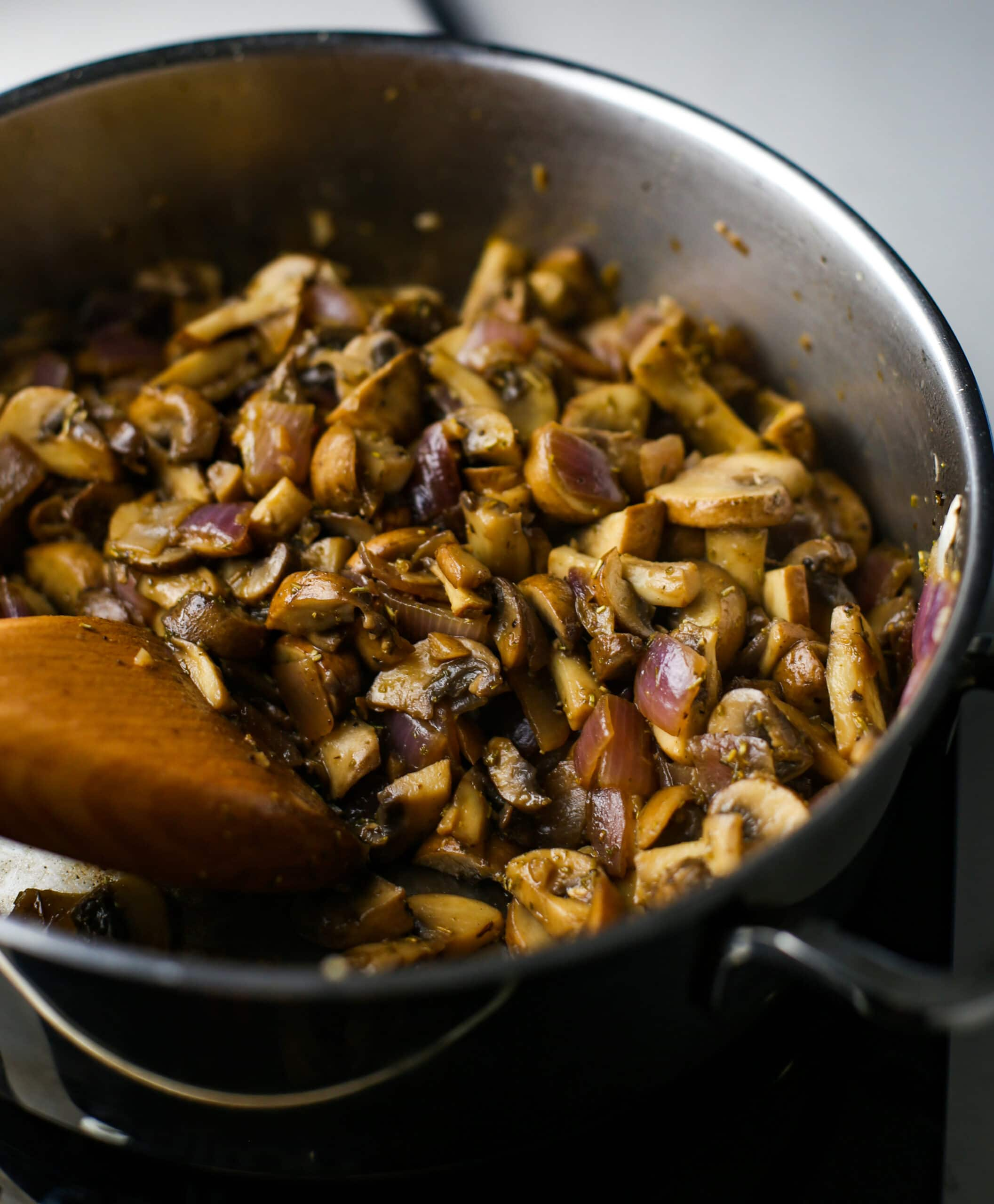 Sauteed browned sliced cremini mushrooms and red onions in a stainless steel saucepan.