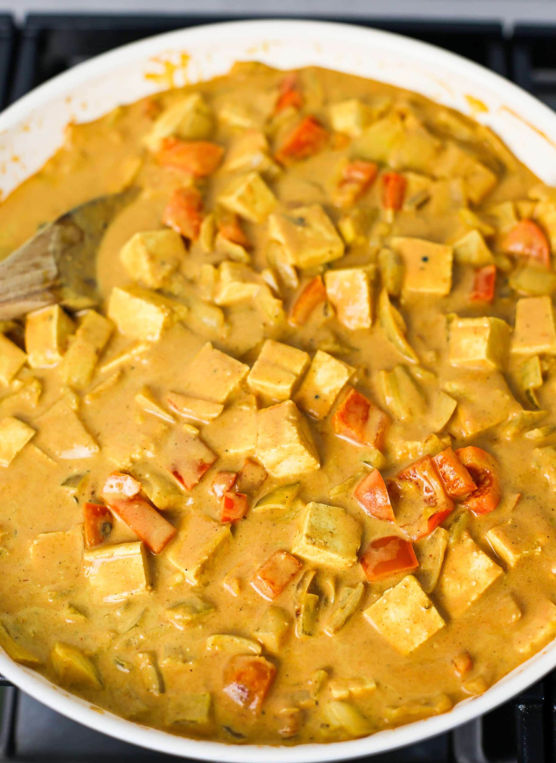 Creamy coconut curry sauce mixed with cubed tofu, and vegetables in a large fry pan.
