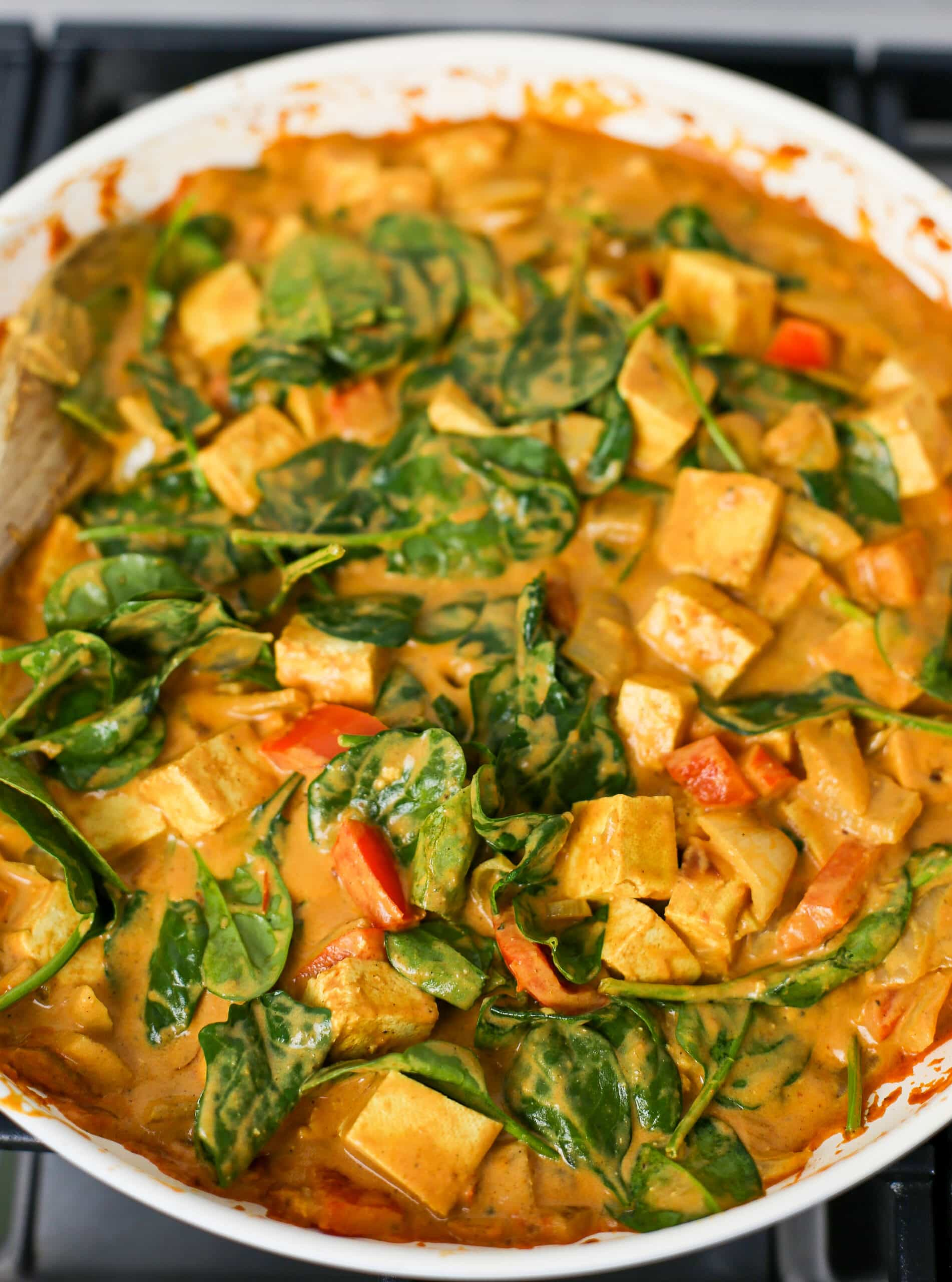 Creamy tofu coconut curry with wilted spinach in a large skillet.
