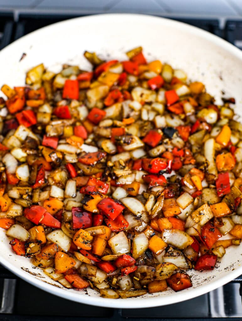 Sautéed chopped white onions, bell peppers, minced garlic, seasonings, and balsamic vinegar in a white frying pan.