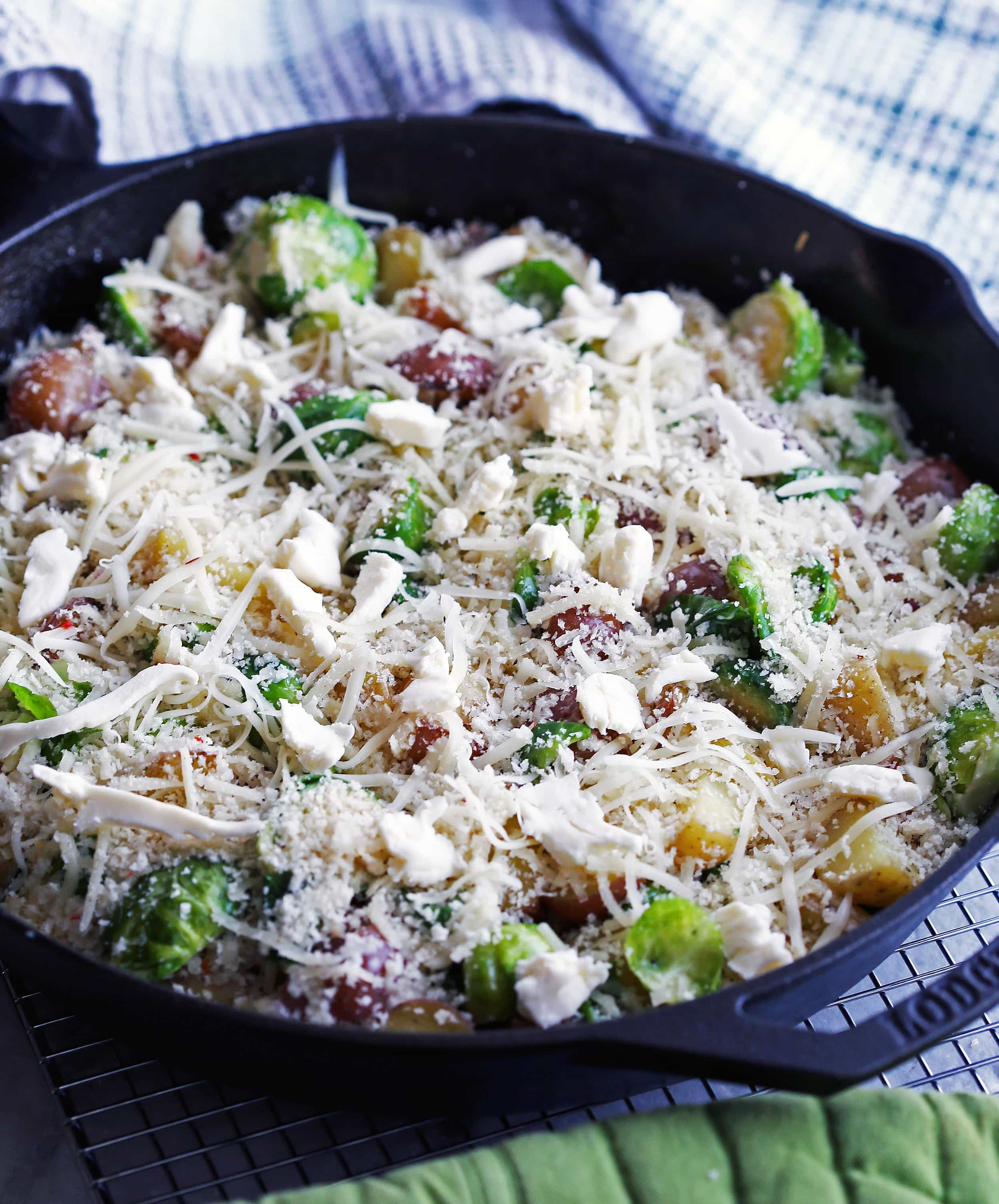 Sautéed onions, baby potatoes, and Brussels sprouts topped with cheese and breadcrumbs in a cast iron skillet.