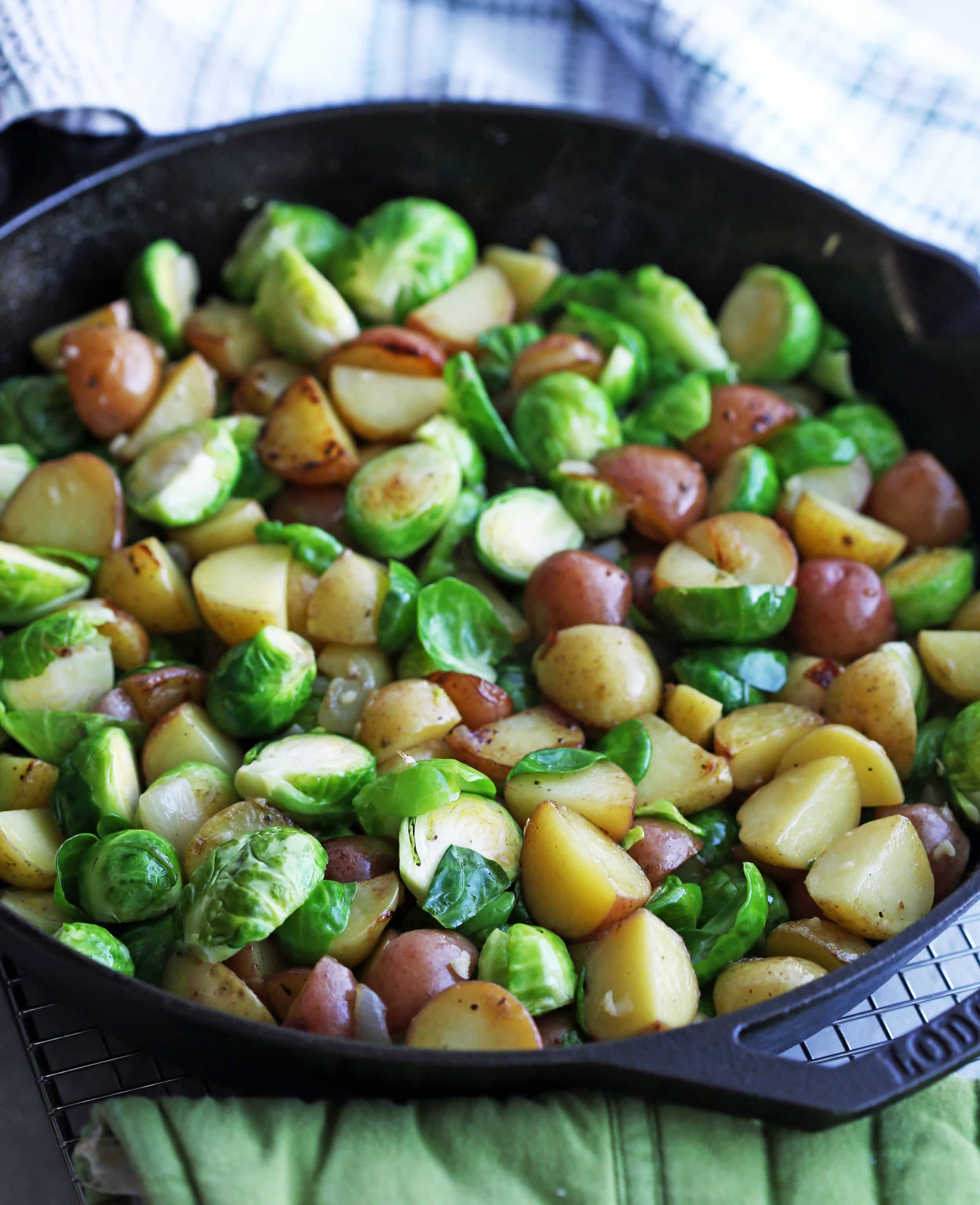 Sautéed onions, chopped baby potatoes, and halved Brussels sprouts in a cast iron skillet.