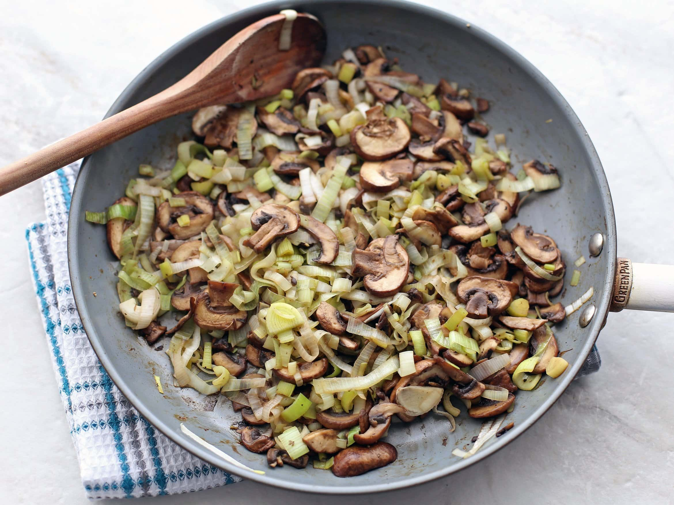 Sautéed leeks and muffins in a frying pan.