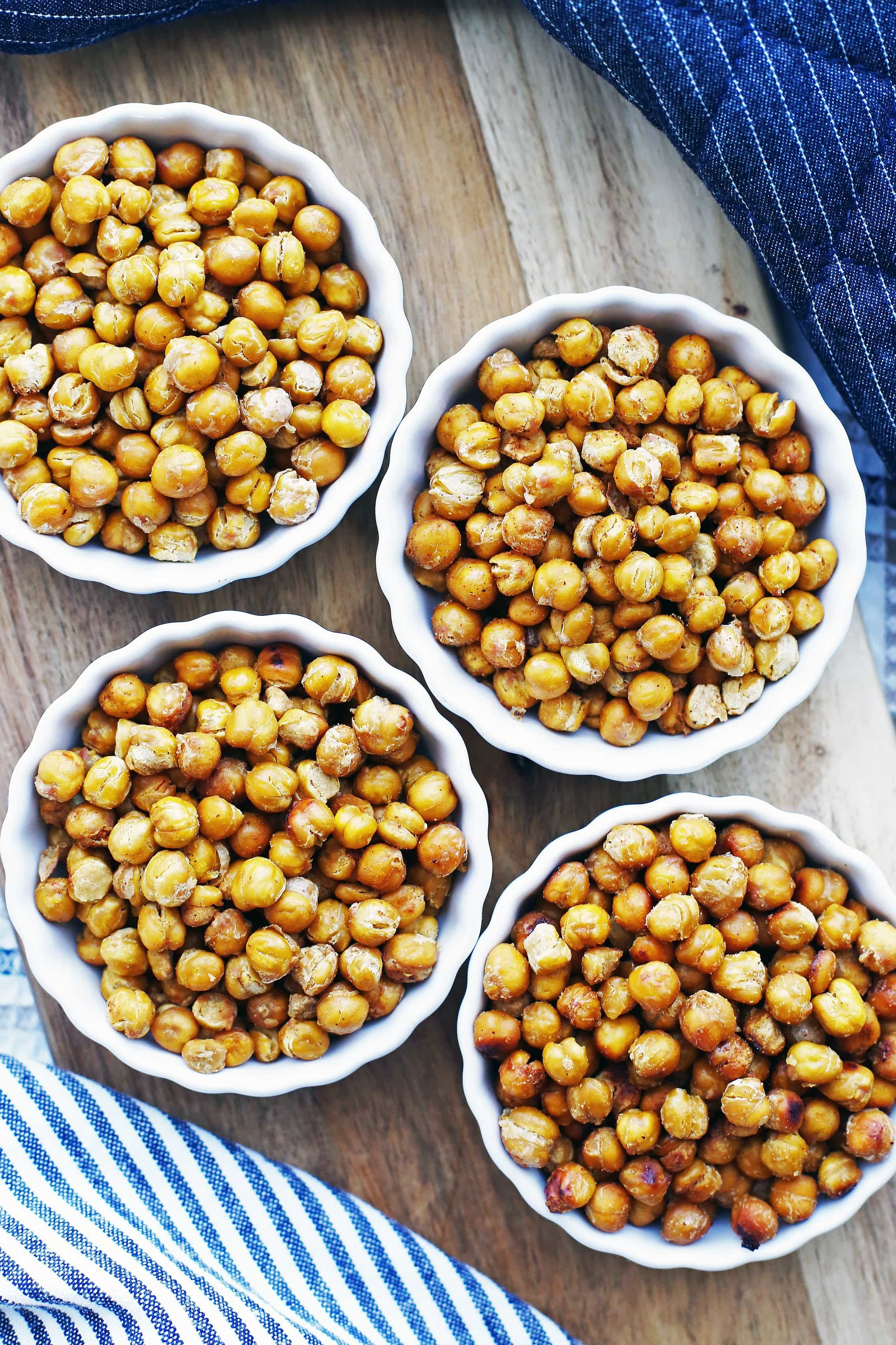 Overhead view of salt and vinegar, taco, honey garlic, and brown sugar lemon roasted chickpeas separated into four porcelain tart pans.