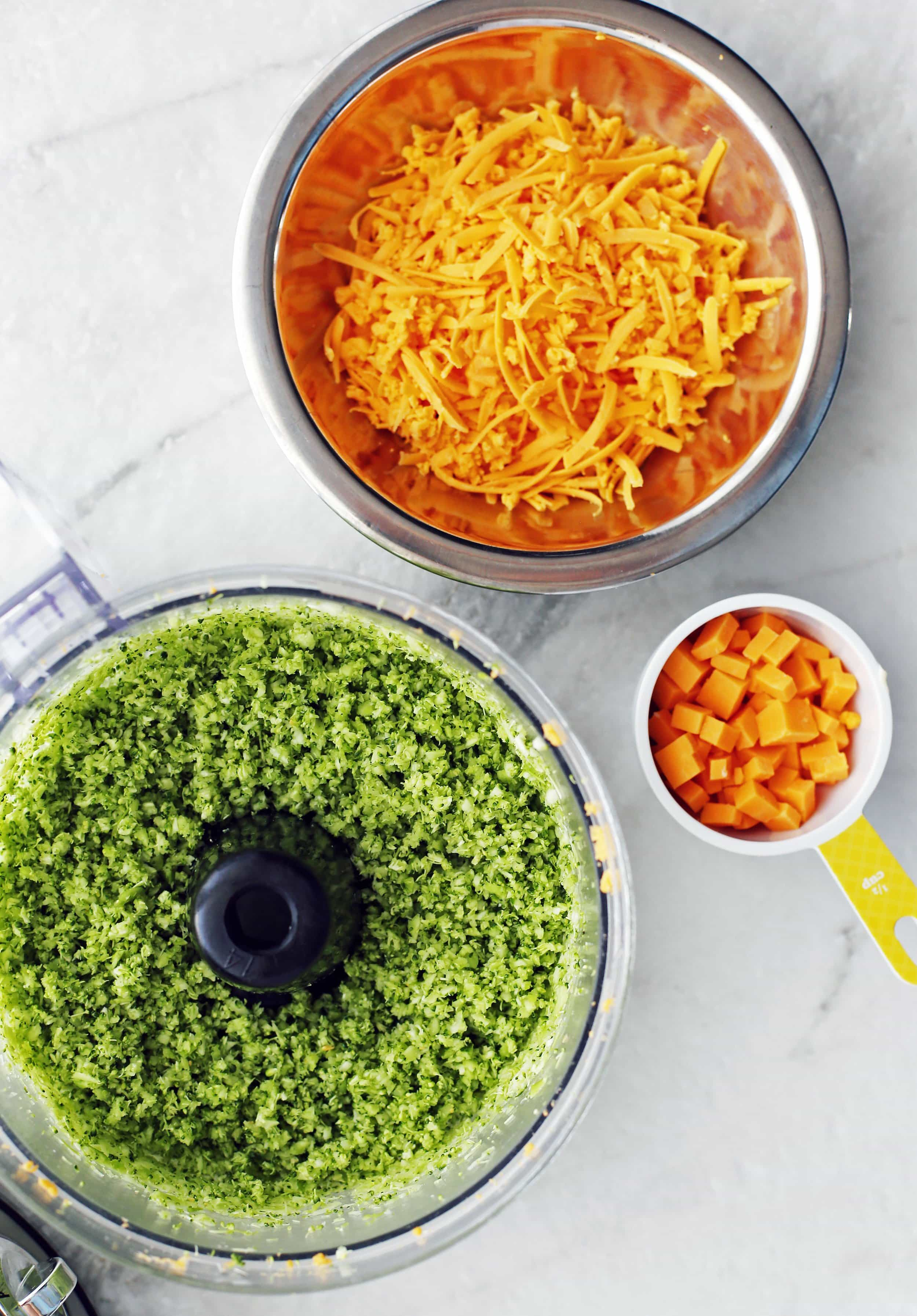 Shredded cheddar cheese, diced cheddar cheese, and finely diced broccoli in bowls.