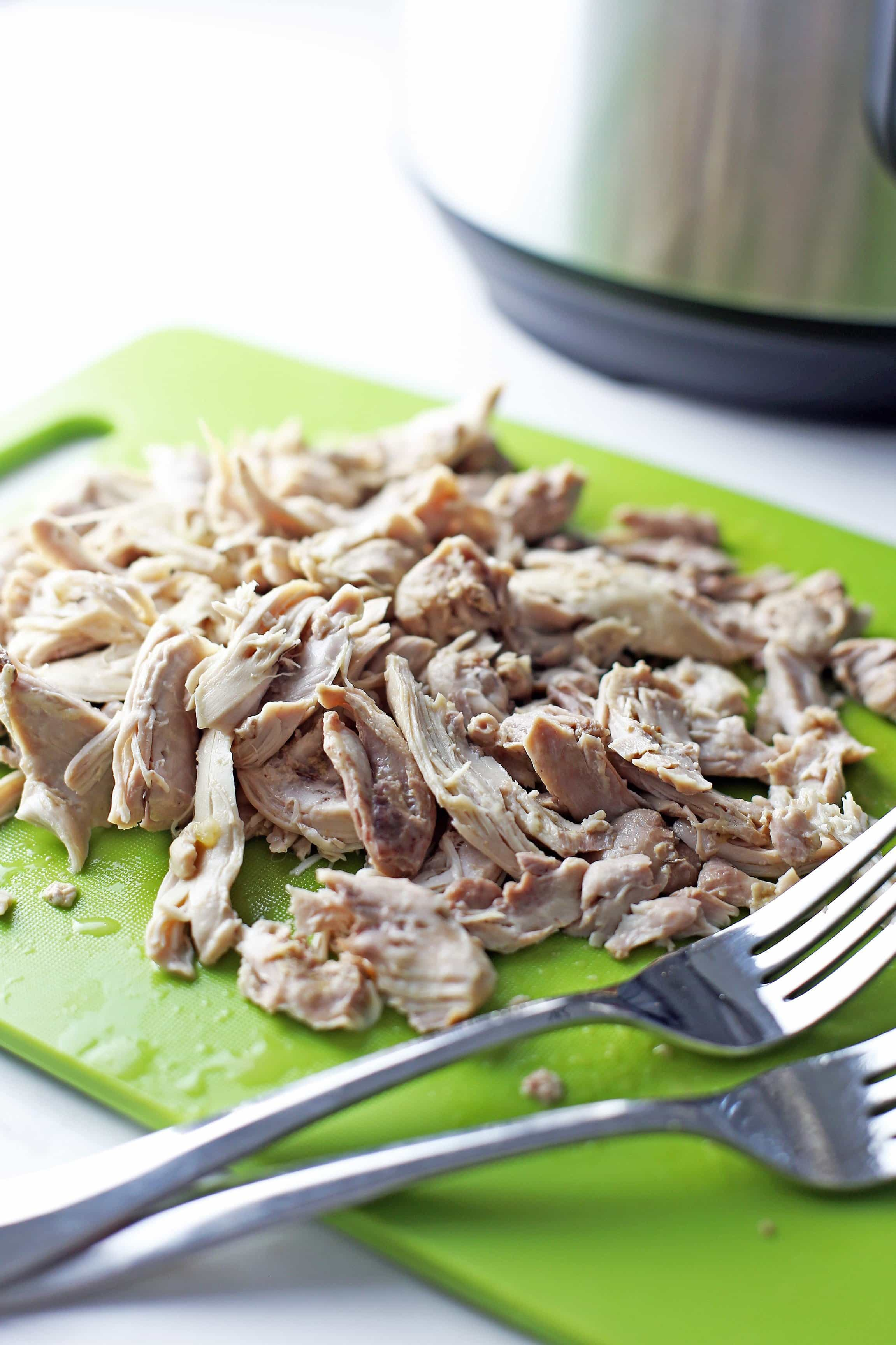 Shredded chicken thighs with two forks on top of green plastic cutting board.