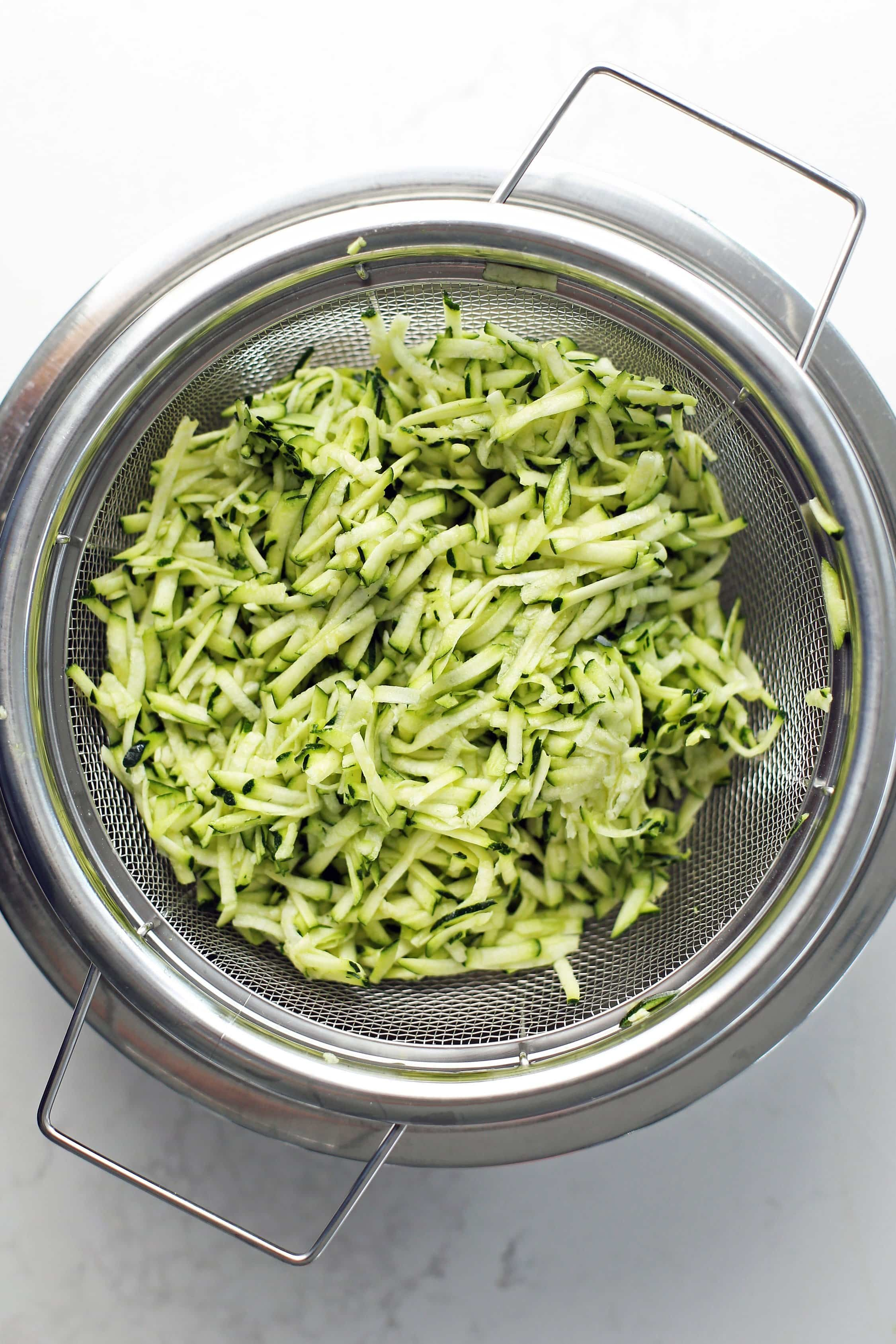 Grated zucchini in a metal mesh strainer with a stainless steel bowl placed below it.