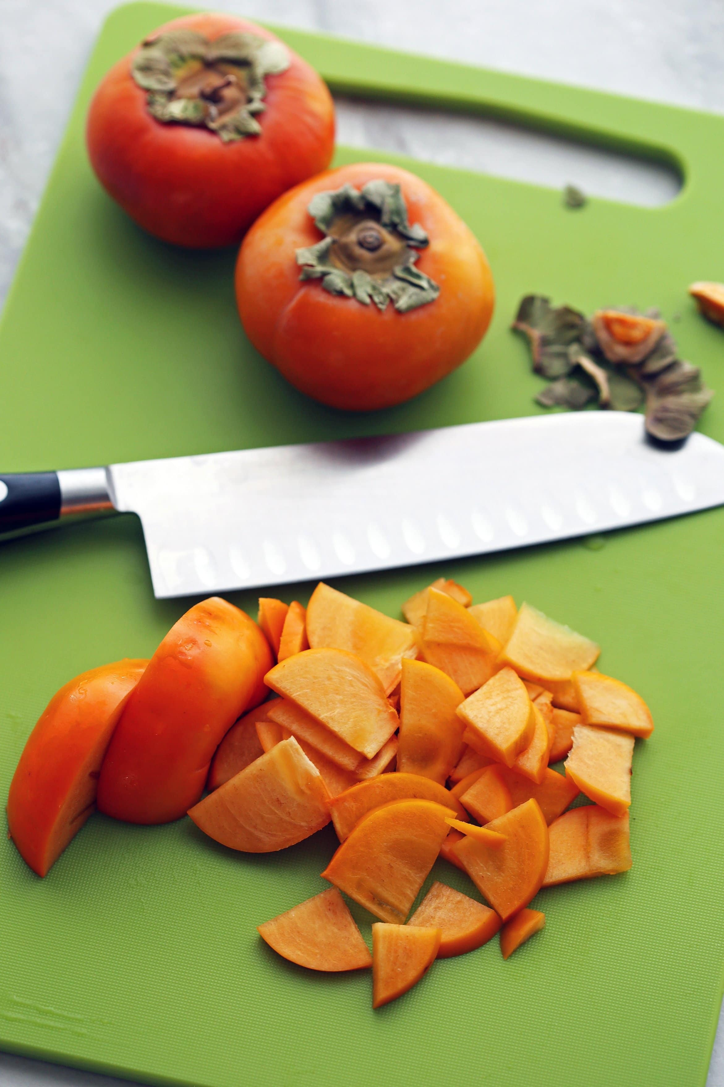 Sliced and whole persimmon fruit and a knife on a green cutting board.