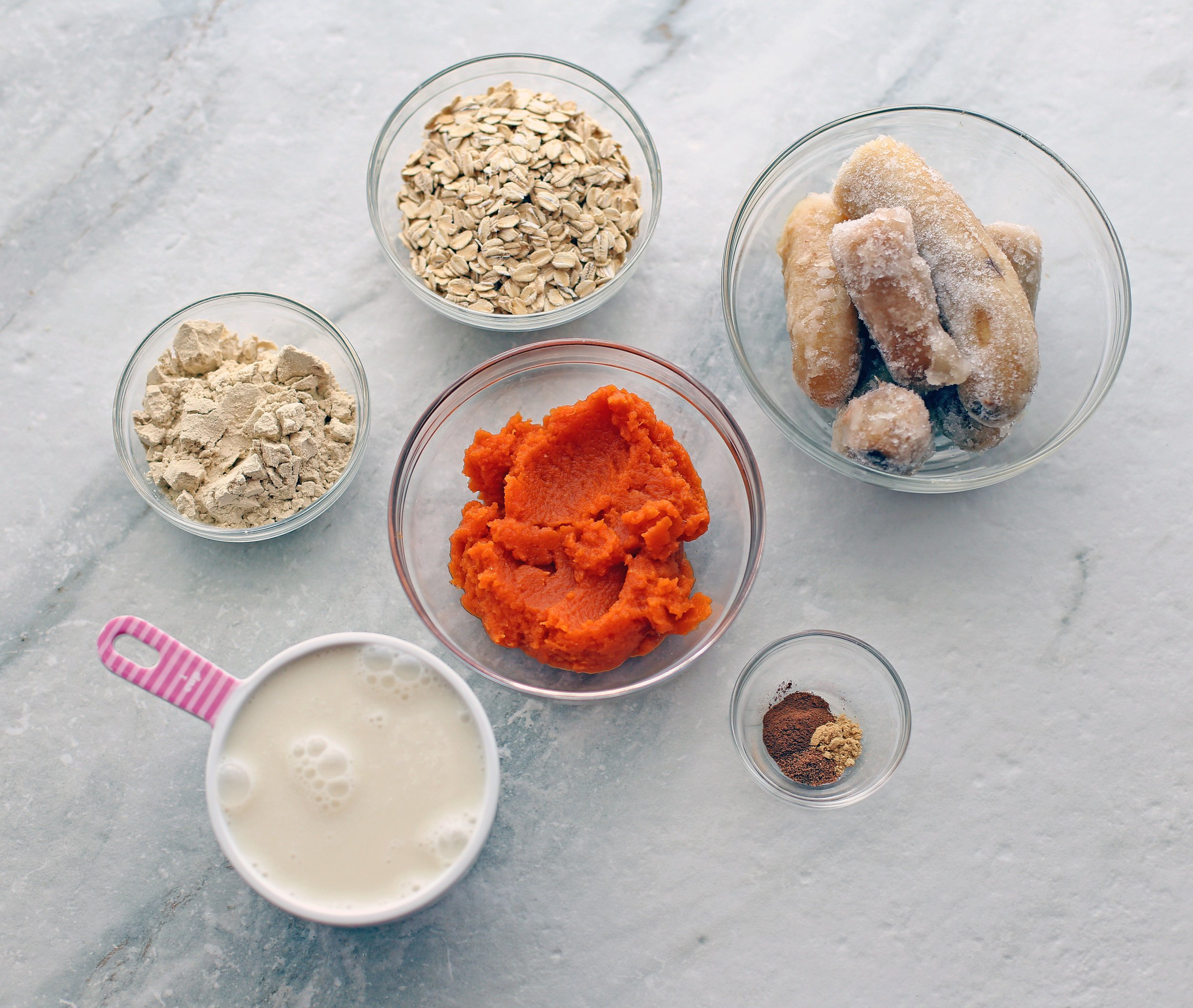 Overhead view of almond milk, pumpkin puree, frozen banana, spices, protein powder, and oatmeal.