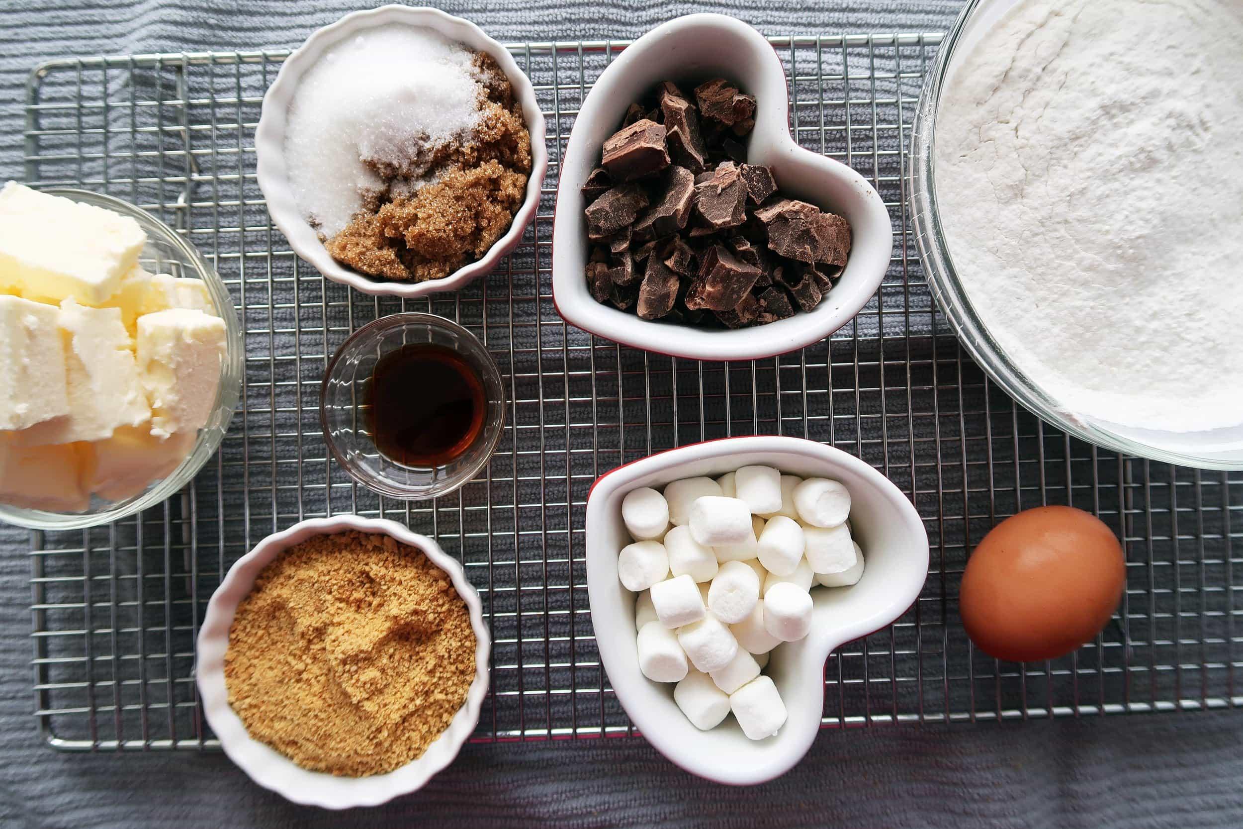 Graham cracker crumbs, marshmallows, chocolate, eggs, butter, flour, sugar, and vanilla.