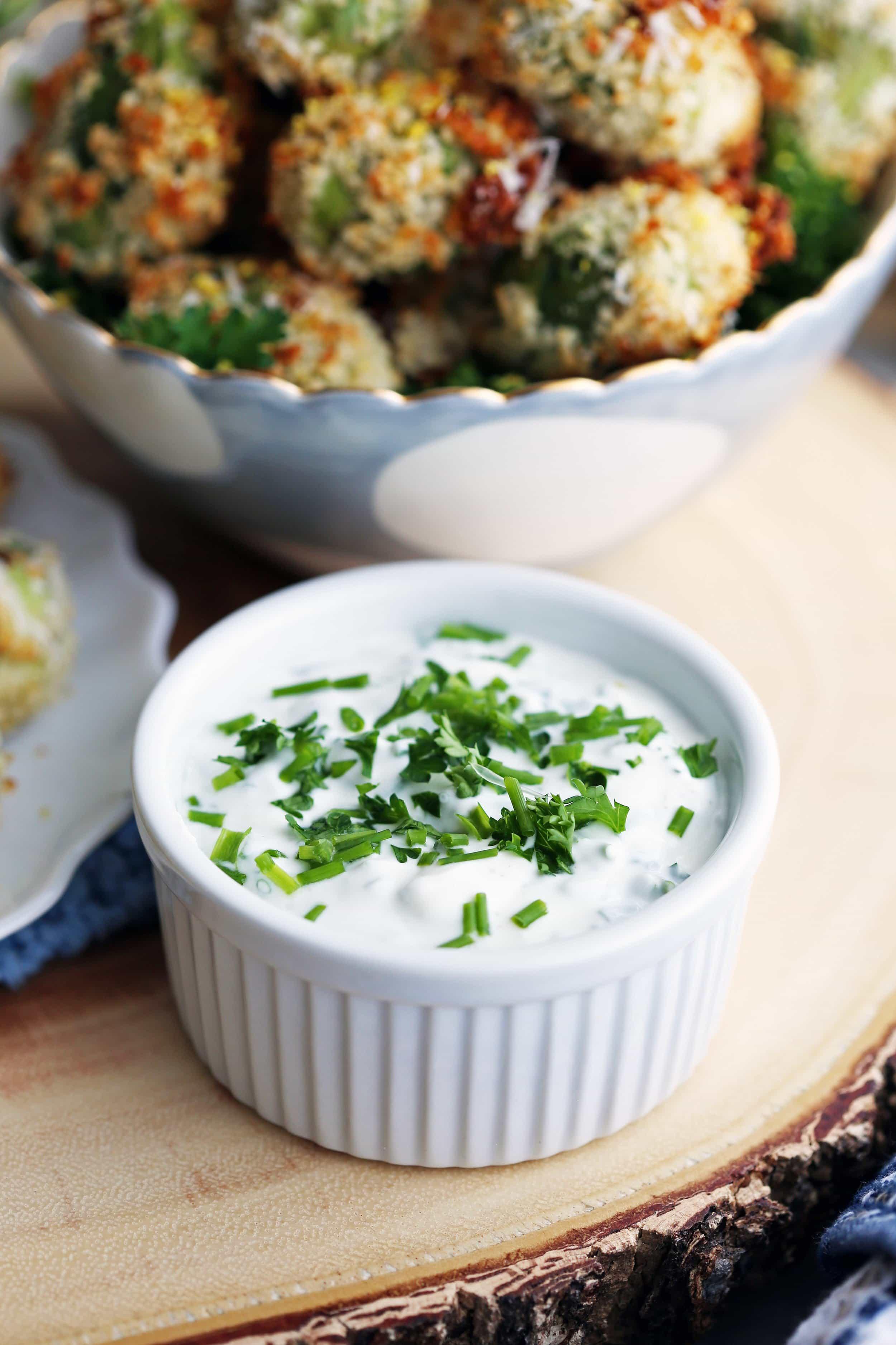 Sour cream herb dip in a white ramekin on wooden platter.