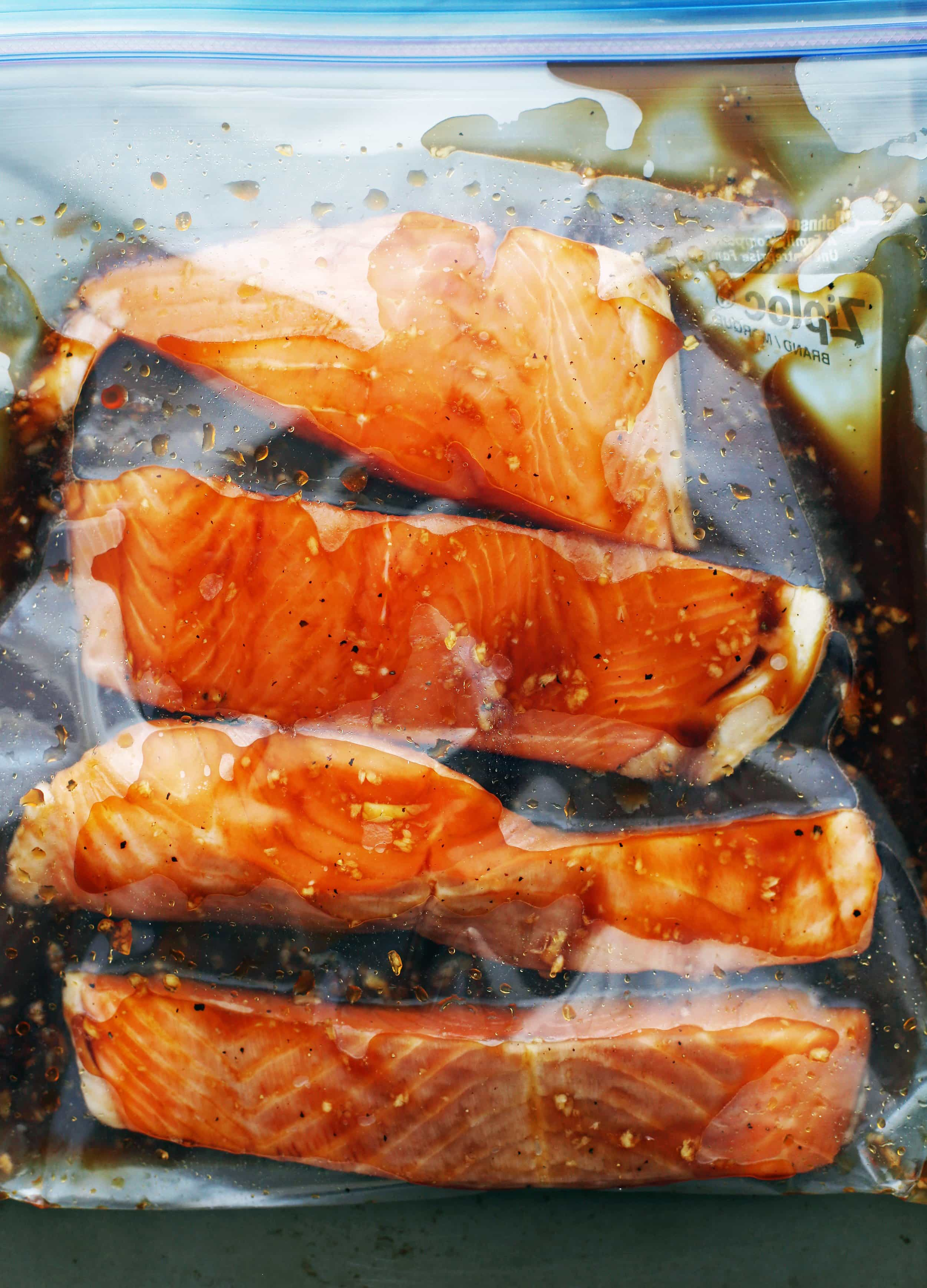 A large resealable plastic bag containing four salmon fillets and soy-maple marinade.