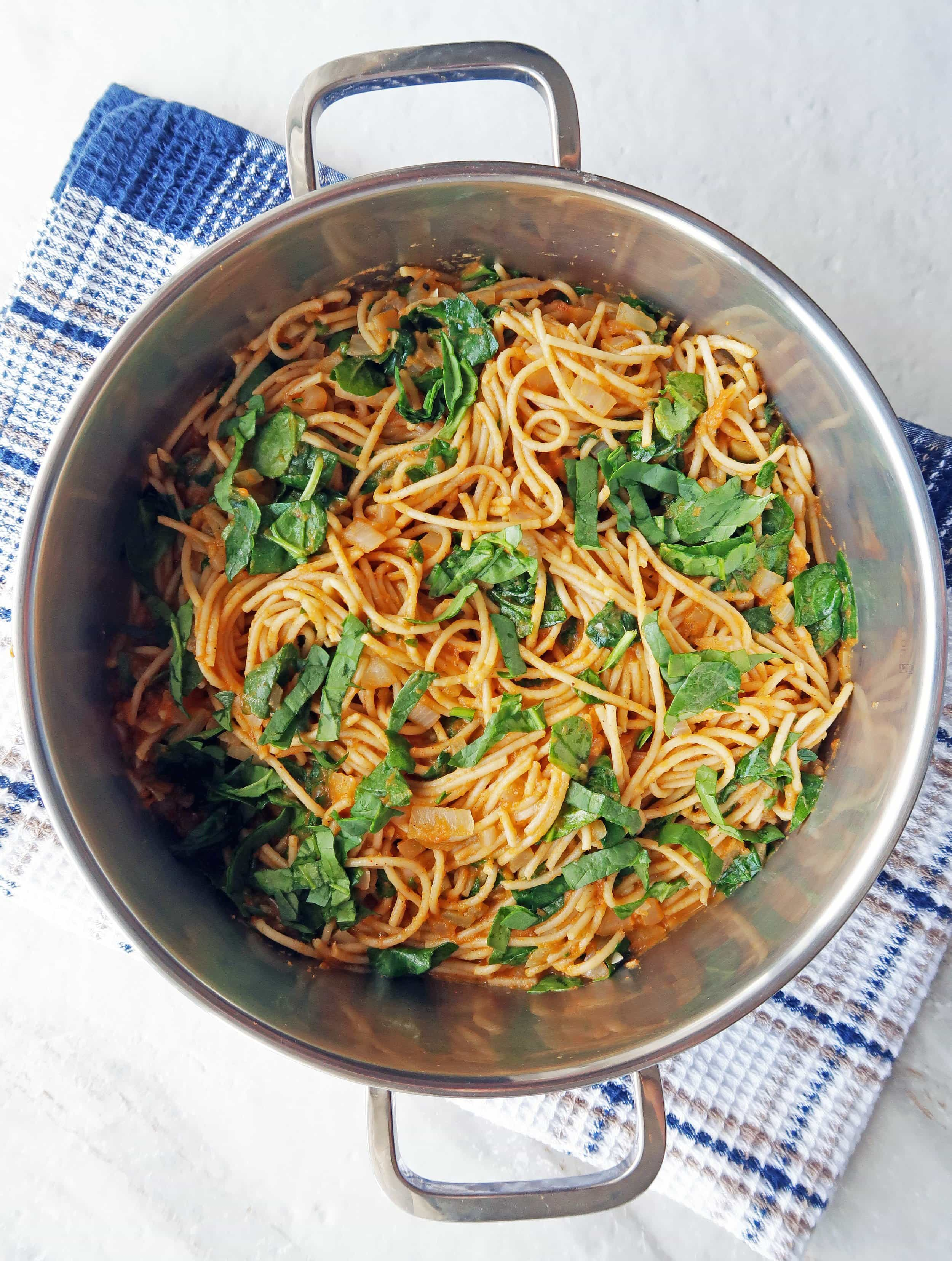 Spaghetti with creamy pumpkin sauce and fresh spinach in a large metal pot.