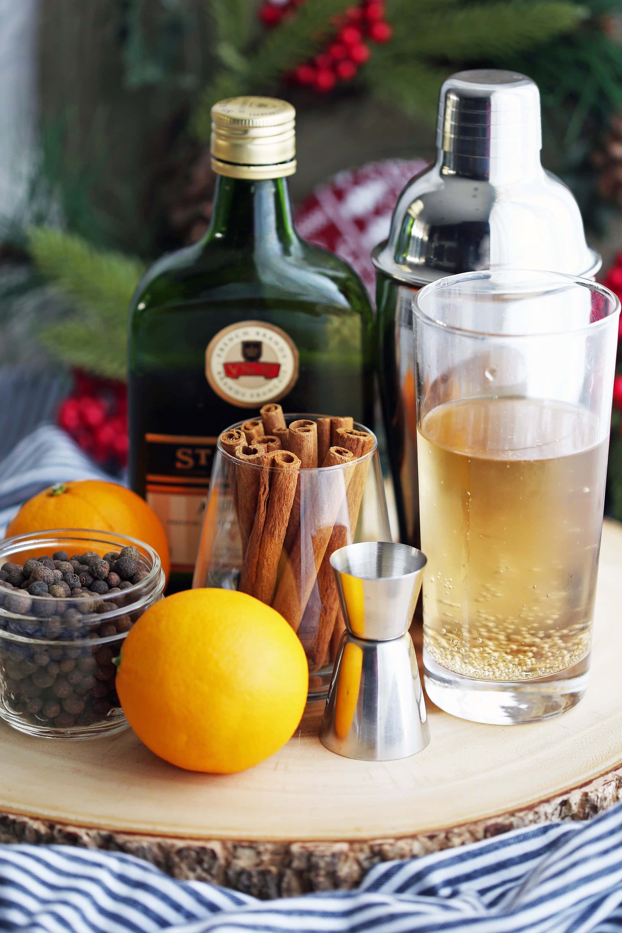 Whole allspice berries, cinnamon sticks, a bottle of Brandy, an orange, a glass of ginger ale, and a cocktail shaker on a wooden platter.