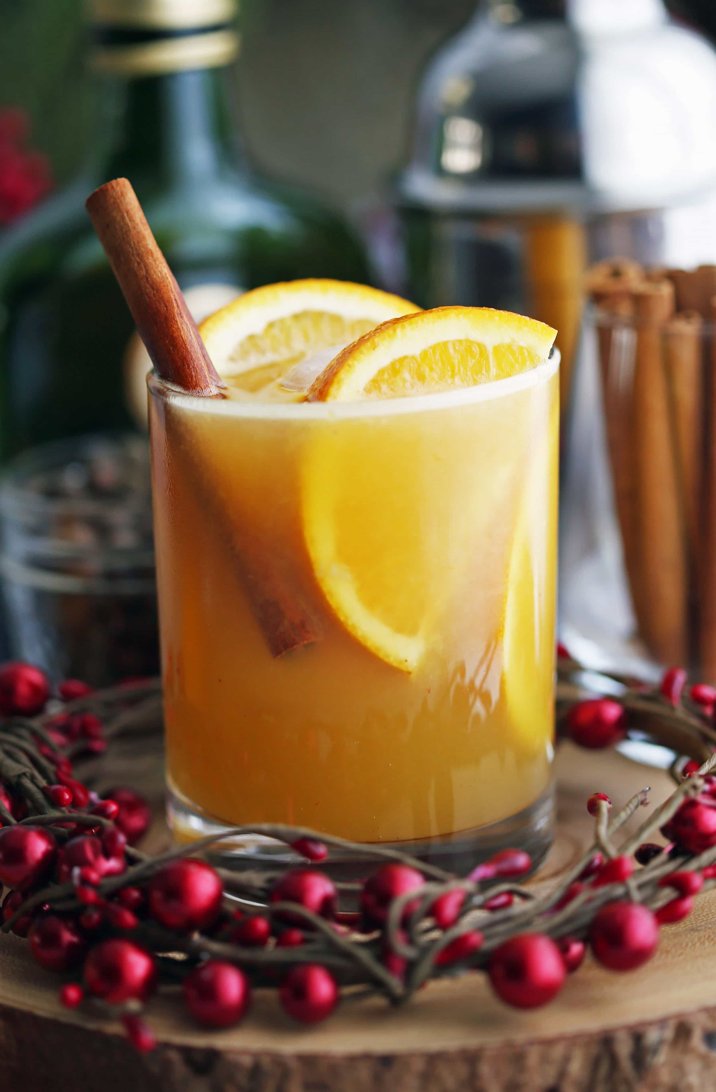Spiced orange brandy spritzer drink with orange slices and a cinnamon stick in a double old fashioned glass.