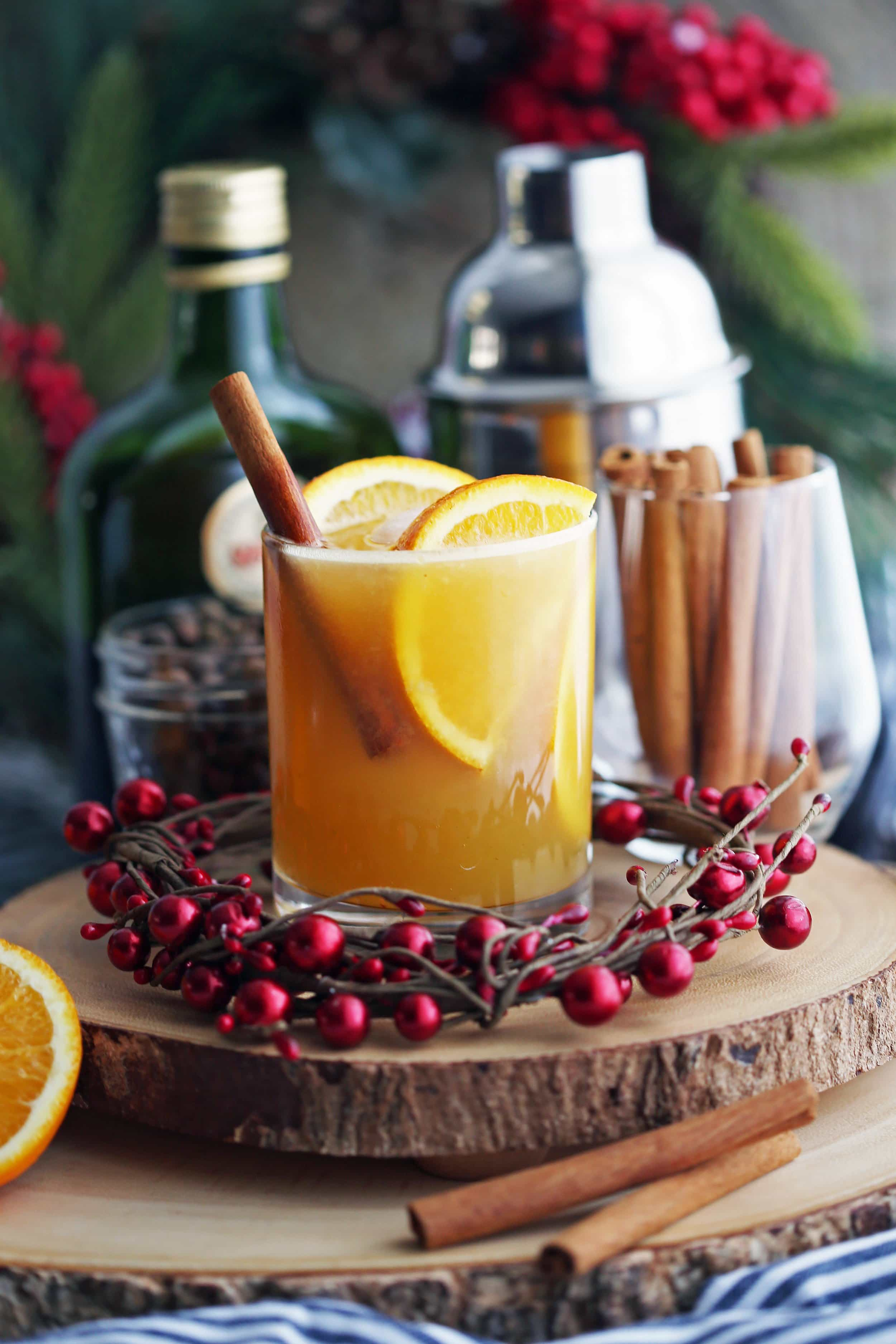 A wooden platter containing a glass of spiced orange brandy spritzer cocktail with orange slices and a cinnamon stick.