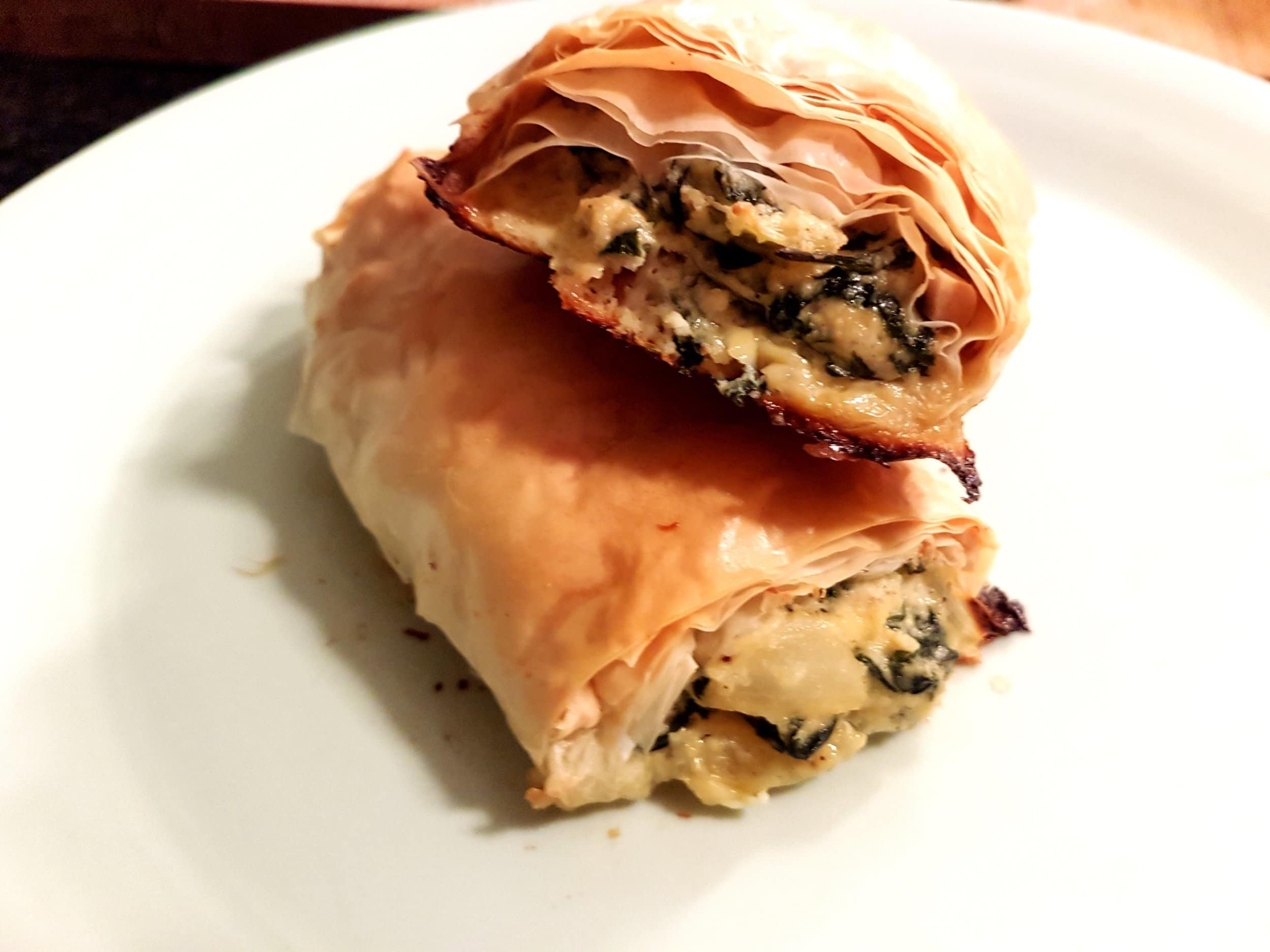 Two Spanakopita Rolls stacked on top of each other.