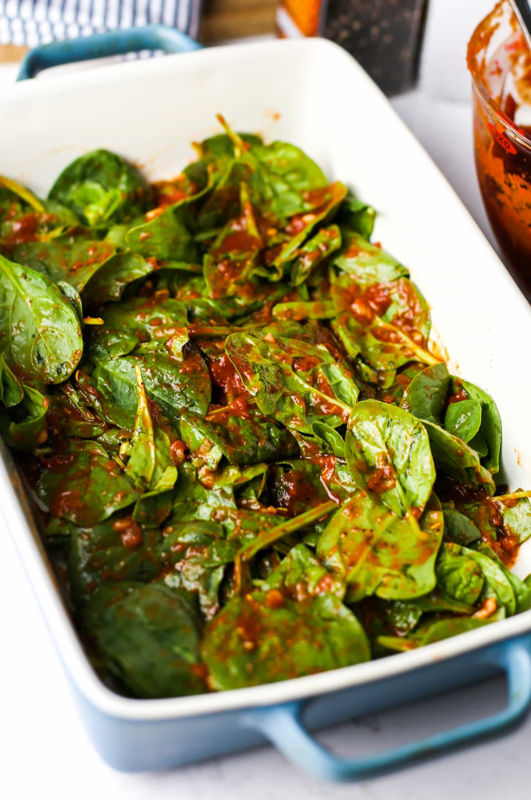 Marinara sauce mixed with fresh baby spinach in blue and white rectangular casserole dish.