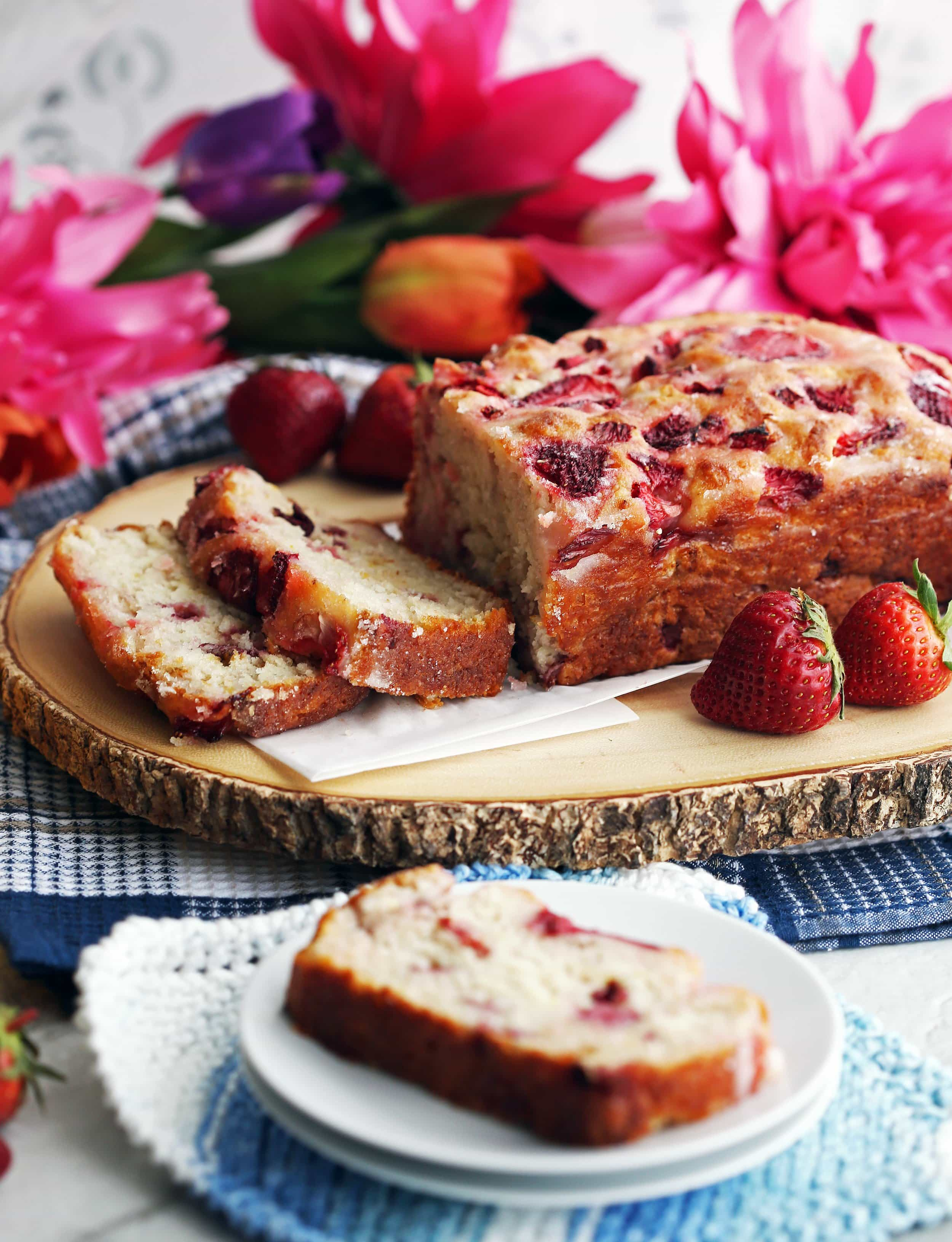 A freshly baked loaf of Strawberry Lemon Yogurt Quick Bread on a large wooden platter.