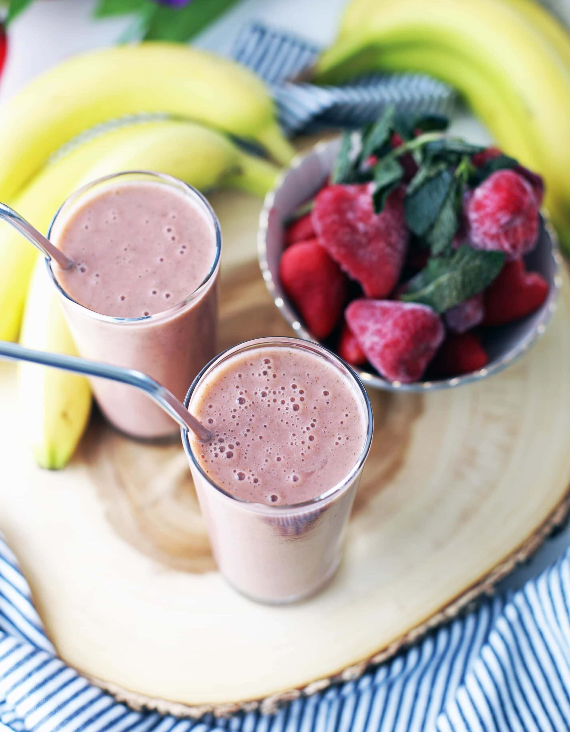 Two strawberry mint smoothies, a bowl of frozen strawberries, and bananas on a wooden platter.
