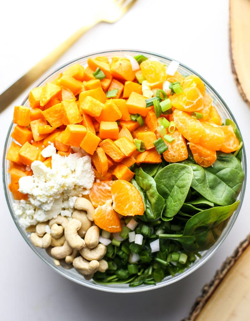 Overhead view of sweet potato salad ingredients in a glass bowl.