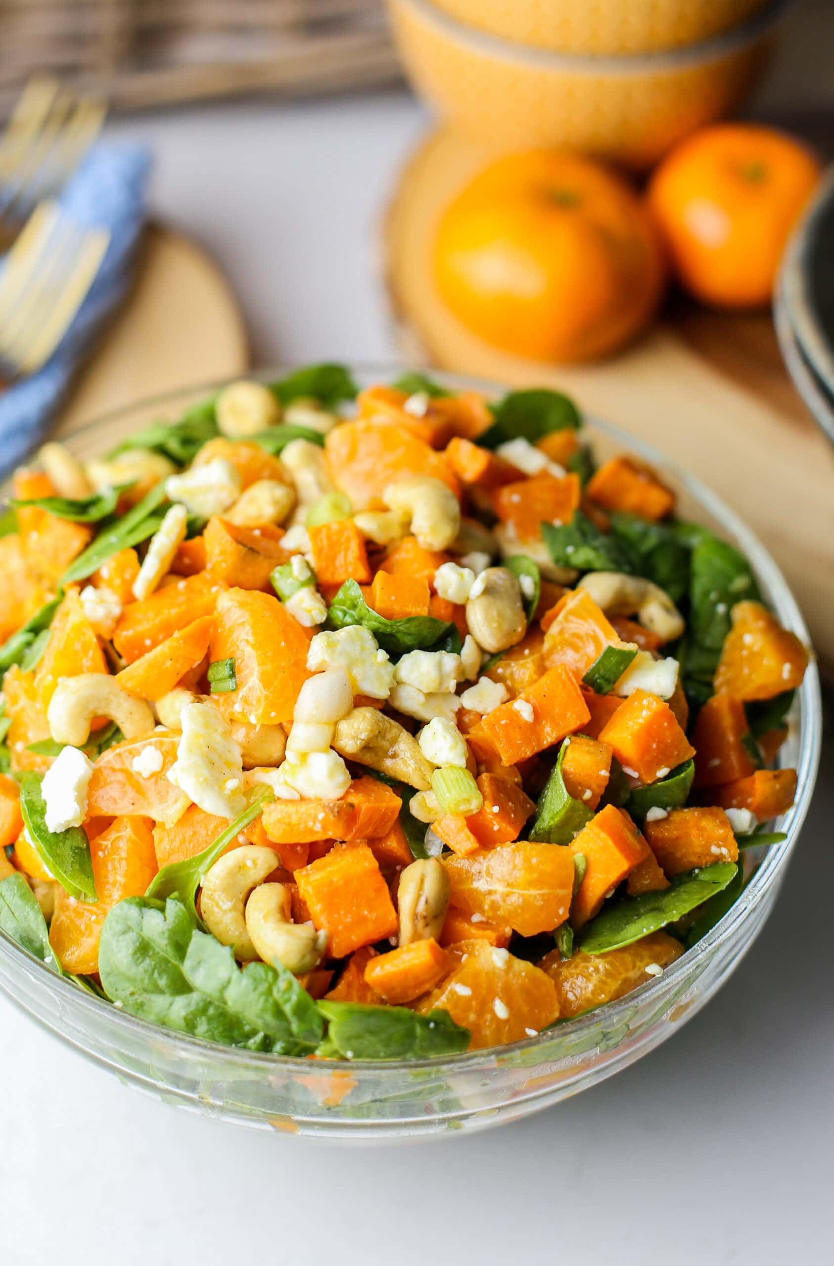 Sweet potato salad with feta, cashews, oranges, and spinach combined in a glass bowl.