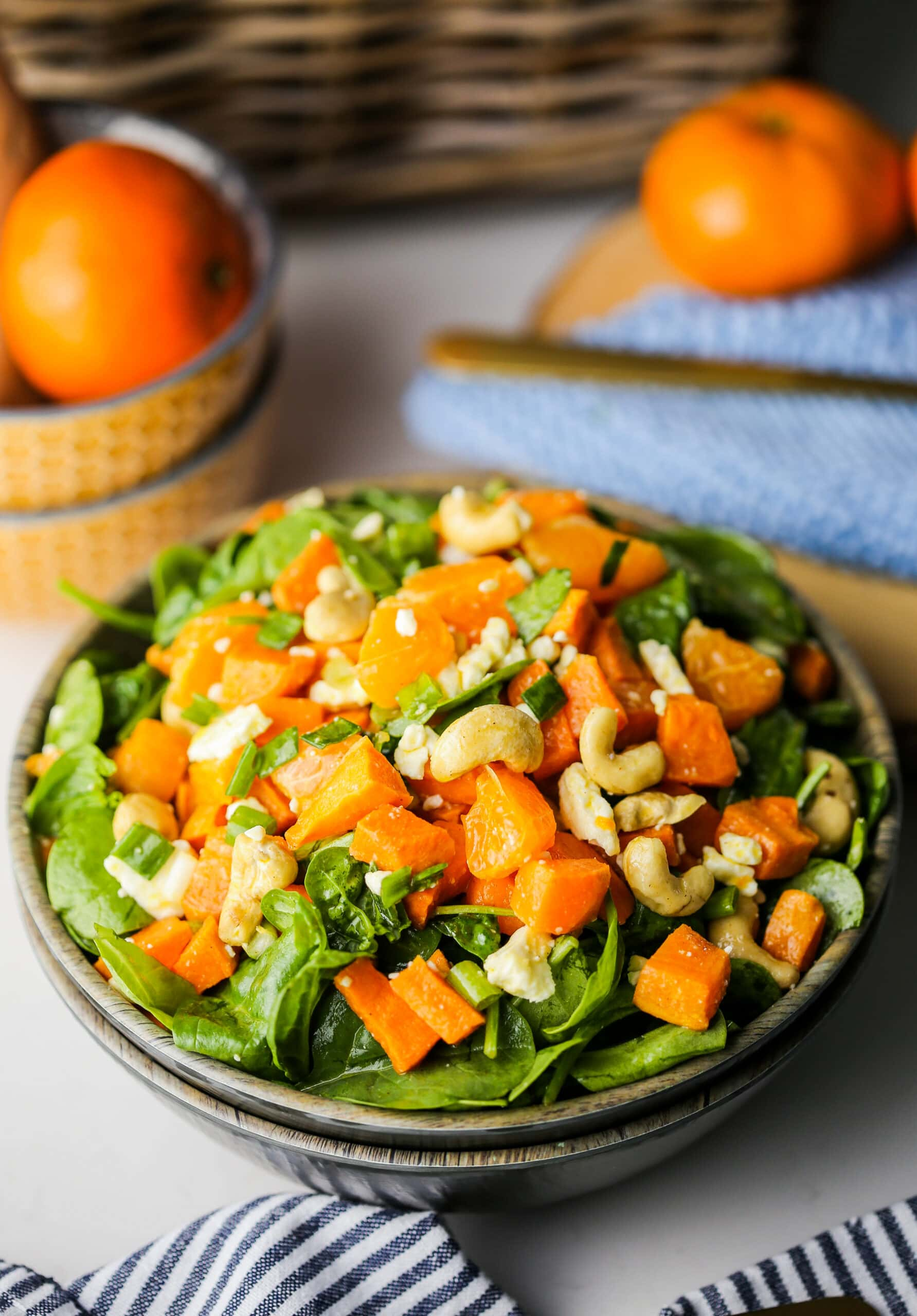 Sweet potato orange spinach salad in a wooden bowl.
