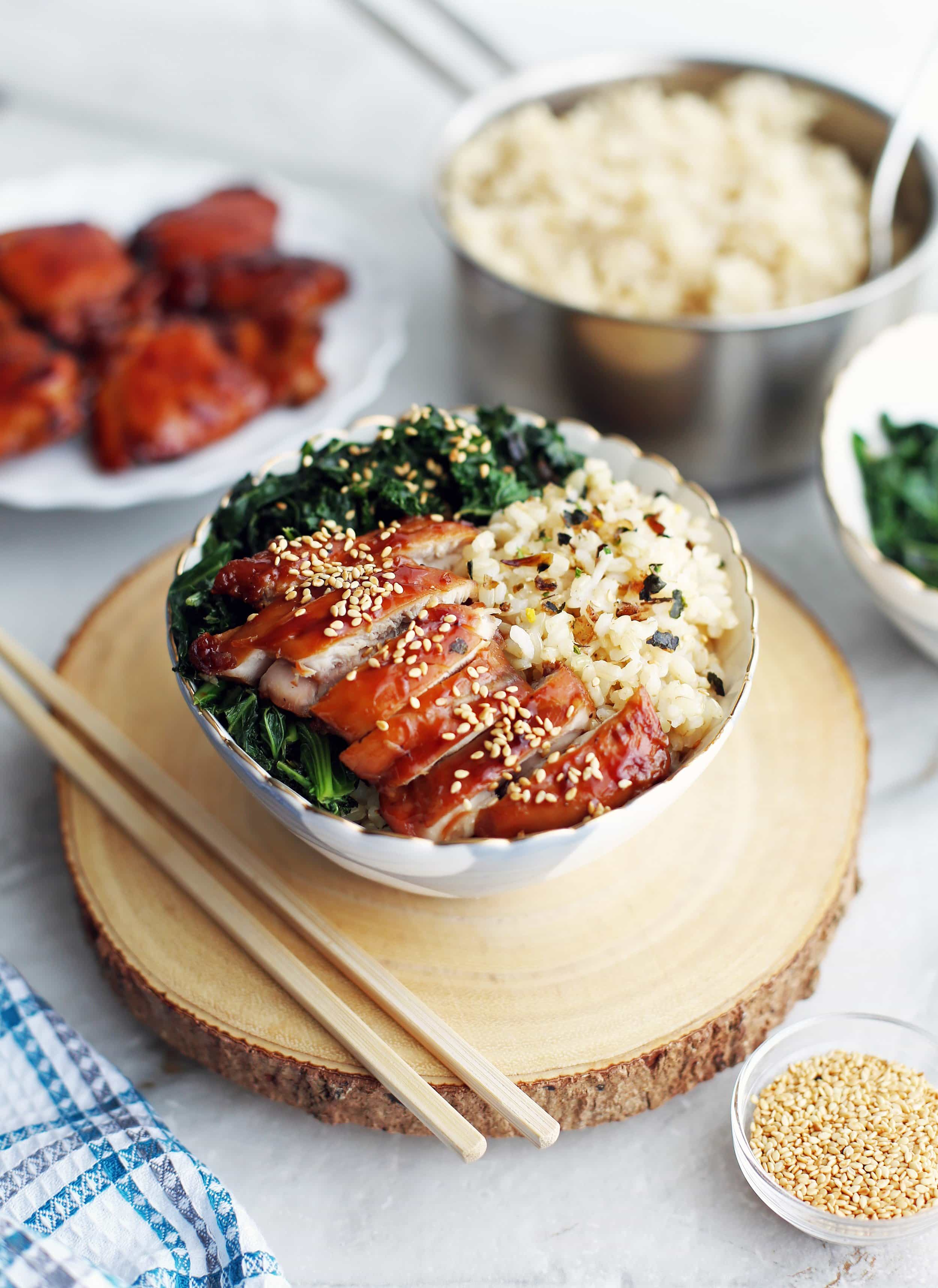 Side view of a bowl of teriyaki chicken with green sauteed kale, and brown rice.