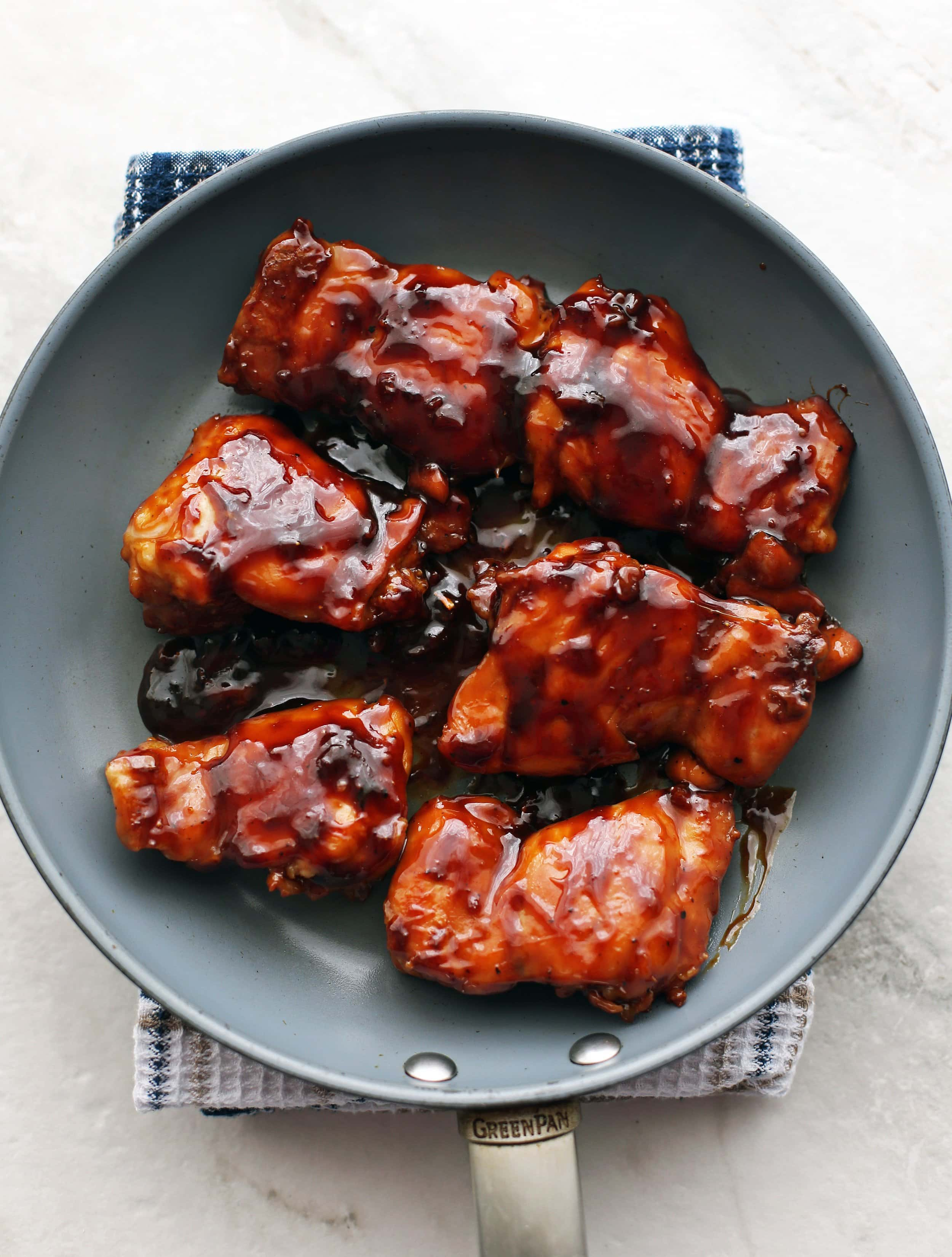 Six pan-cooked chicken thighs covered with teriyaki sauce in a skillet.