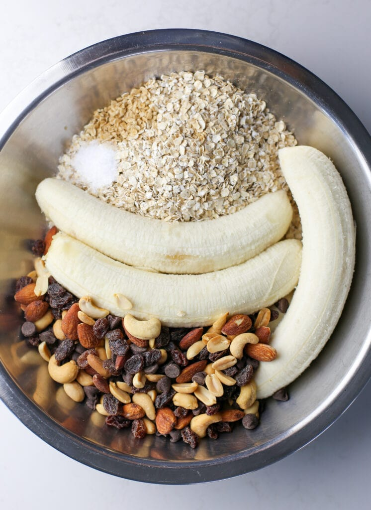 Two peeled bananas, quick oats, trail mix, vanilla extract, and salt in a stainless steel bowl.