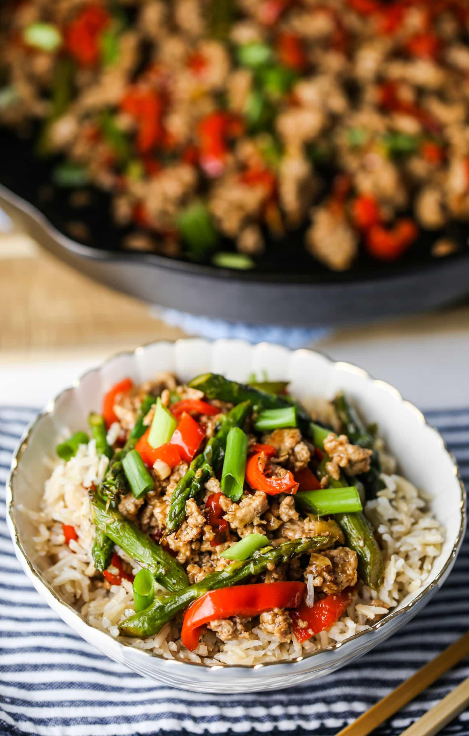 A top angle view of turkey asparagus stir-fry in a blue and white bowl and in a cast iron skillet.