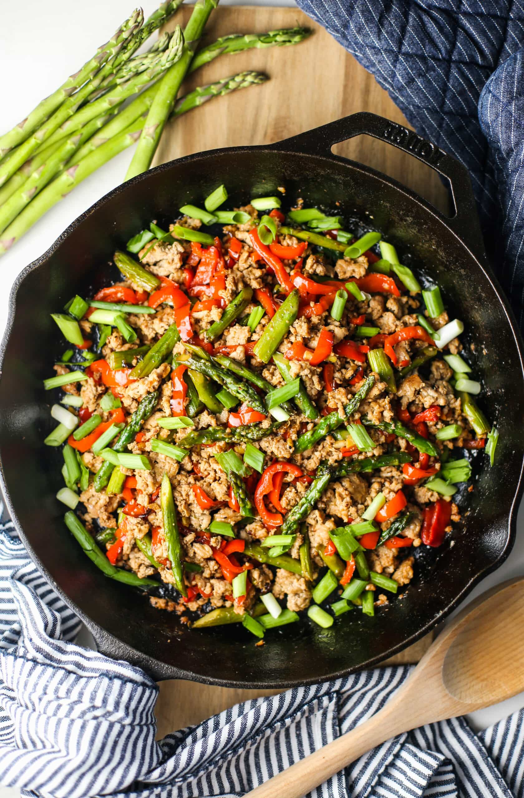 Overhead view of a stir-fry featuring ground turkey, asparagus, and bell pepper in a cast iron skillet.
