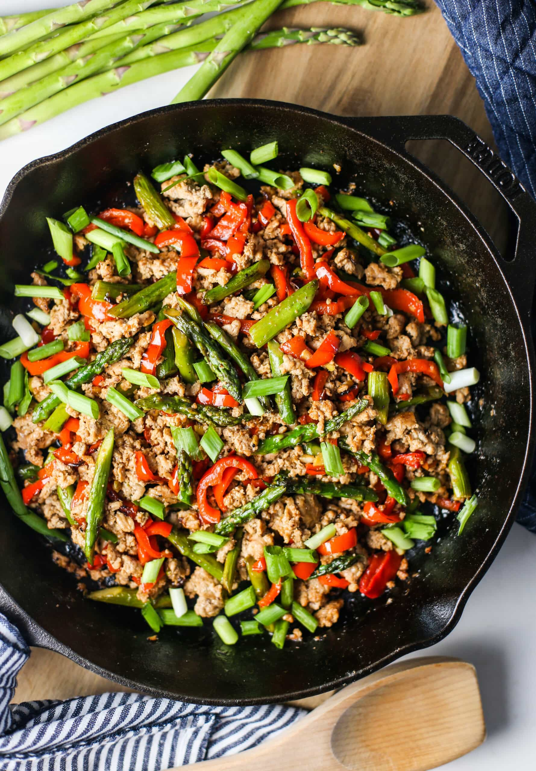 Overhead view of cast iron skillet containing a ground turkey and asparagus stir-fry.