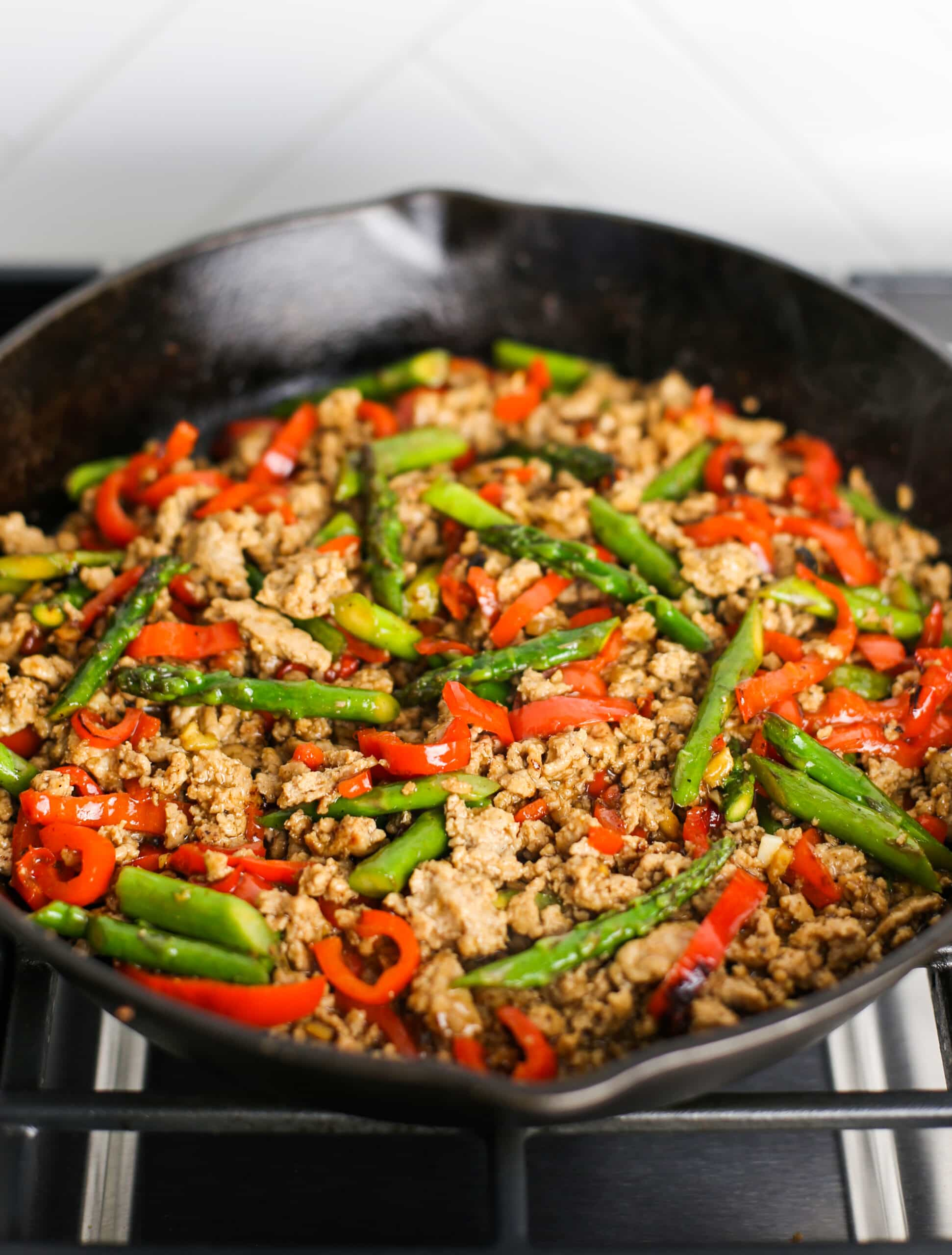 Stir-fried ground turkey, asparagus, and bell pepper in a cast iron skillet.
