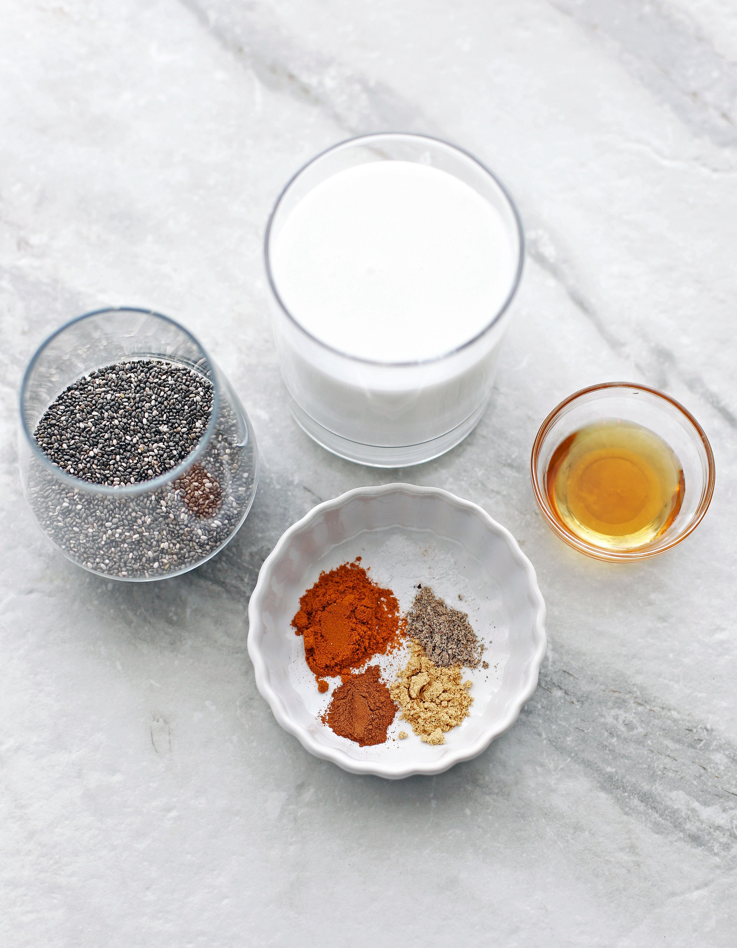 Chia seeds, coconut milk, maple syrup, and spices including turmeric, ginger, cinnamon, and cardamom in glasses and bowls.