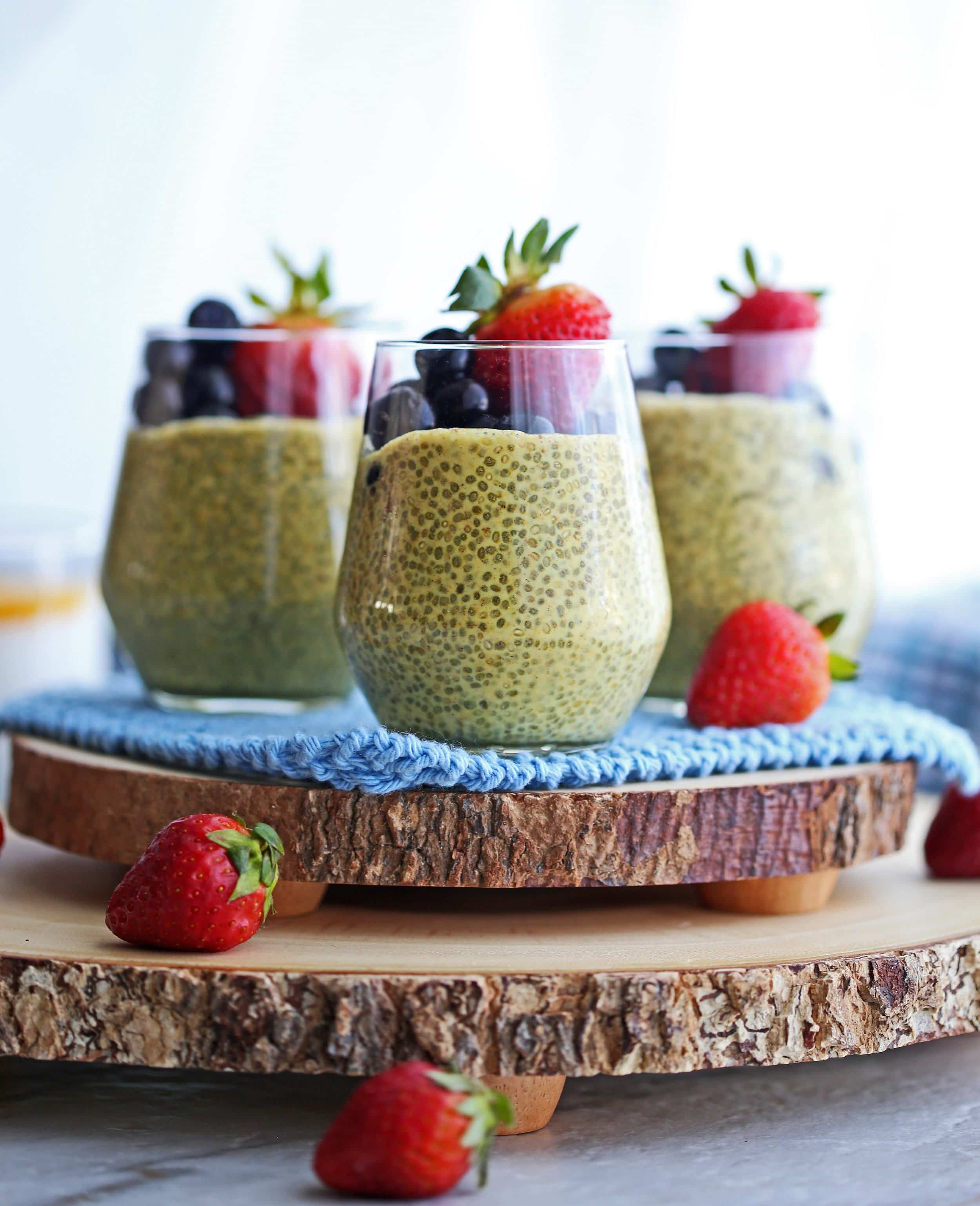 Side view of three glasses full of turmeric milk chia pudding with strawberries and blueberries on a wooden slab.