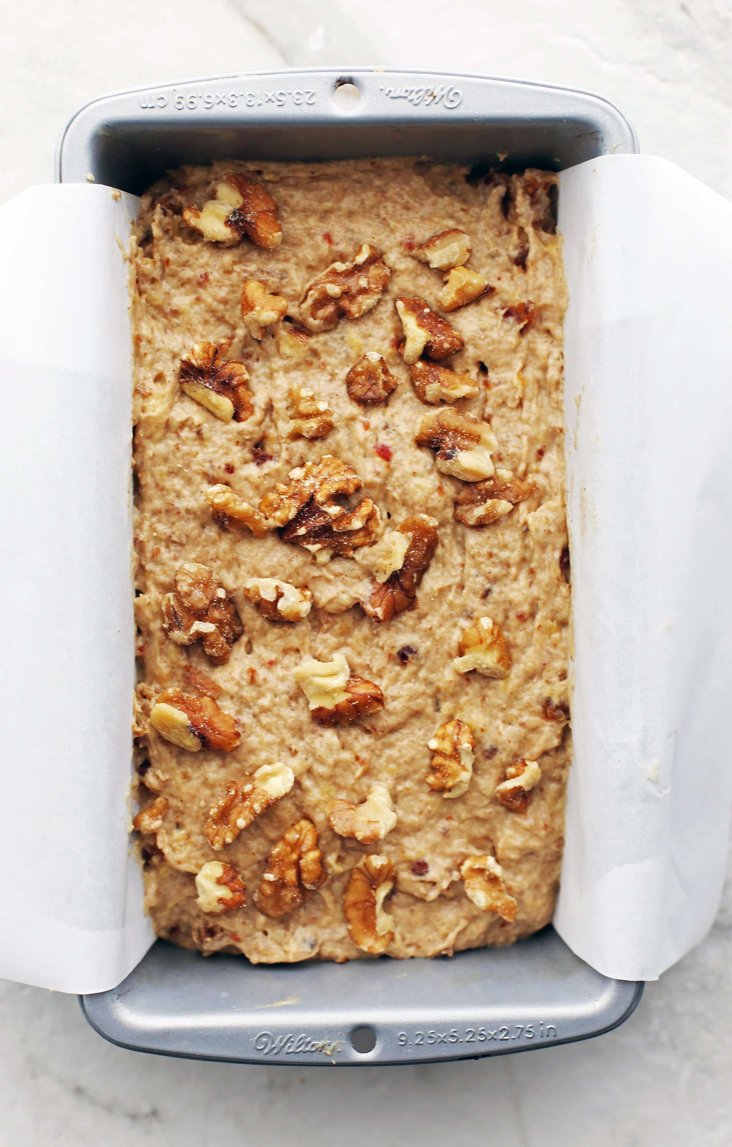 Date Banana Nut Bread dough topped with walnuts in a parchment paper-lined loaf pan.