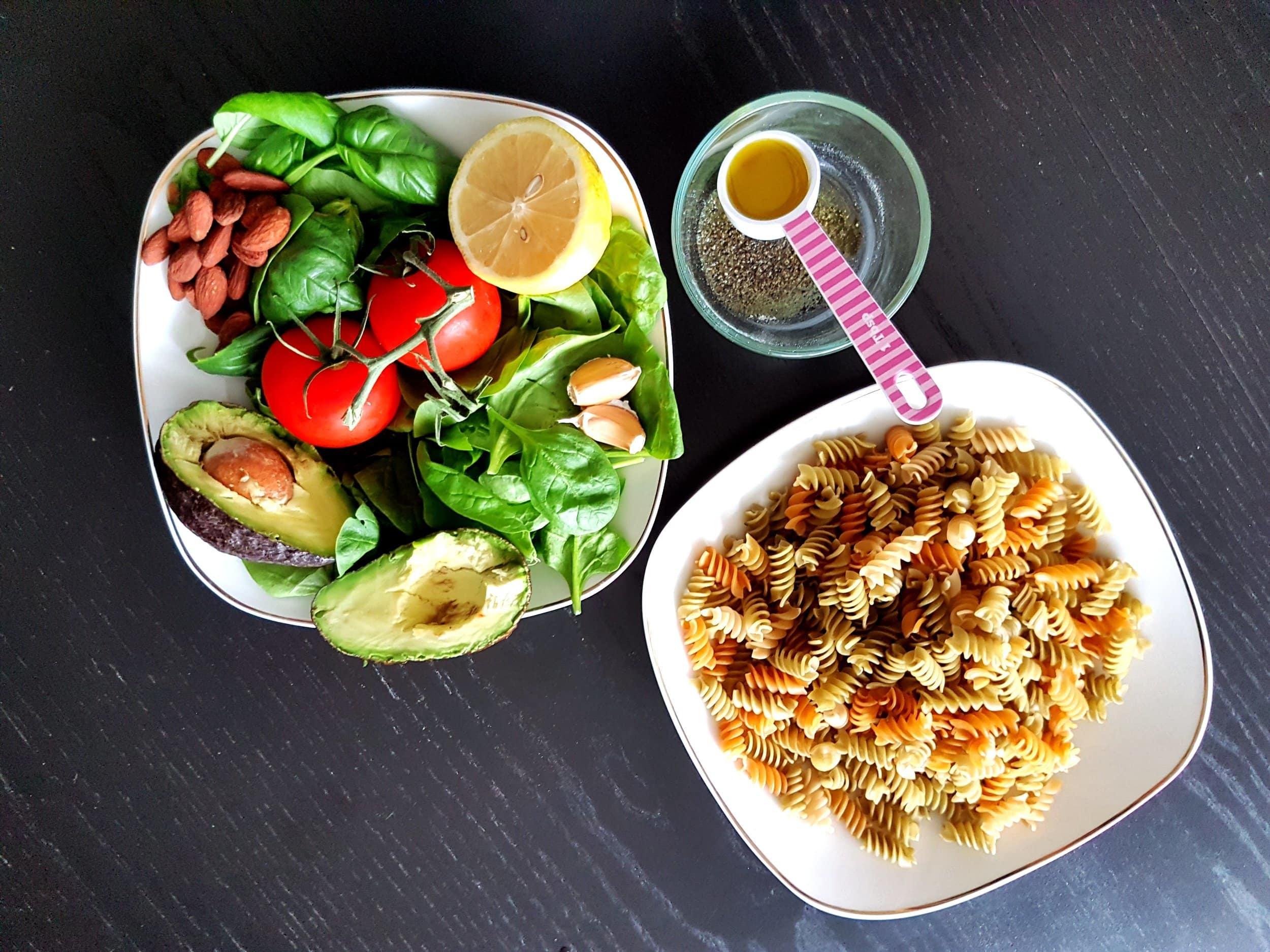Basil, tomatoes, avocado, pasta, a lemon, almonds, and garlic.
