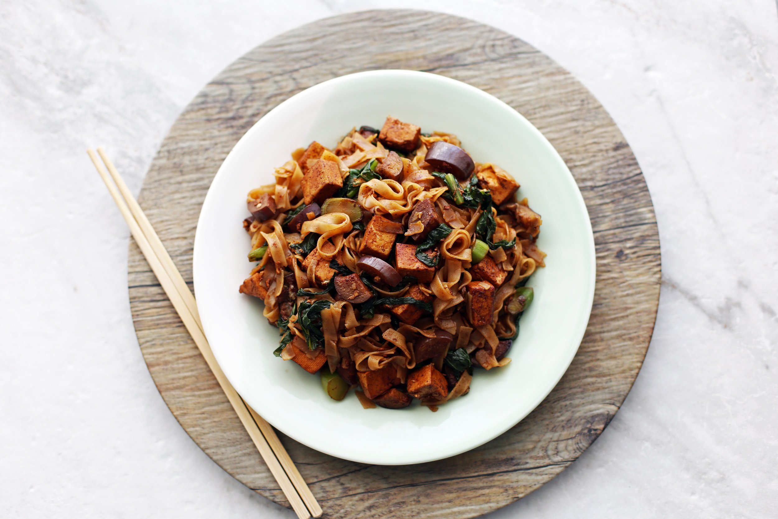 a plate of Vegetarian Pad See Ew topped with Thai basil, ready to eat