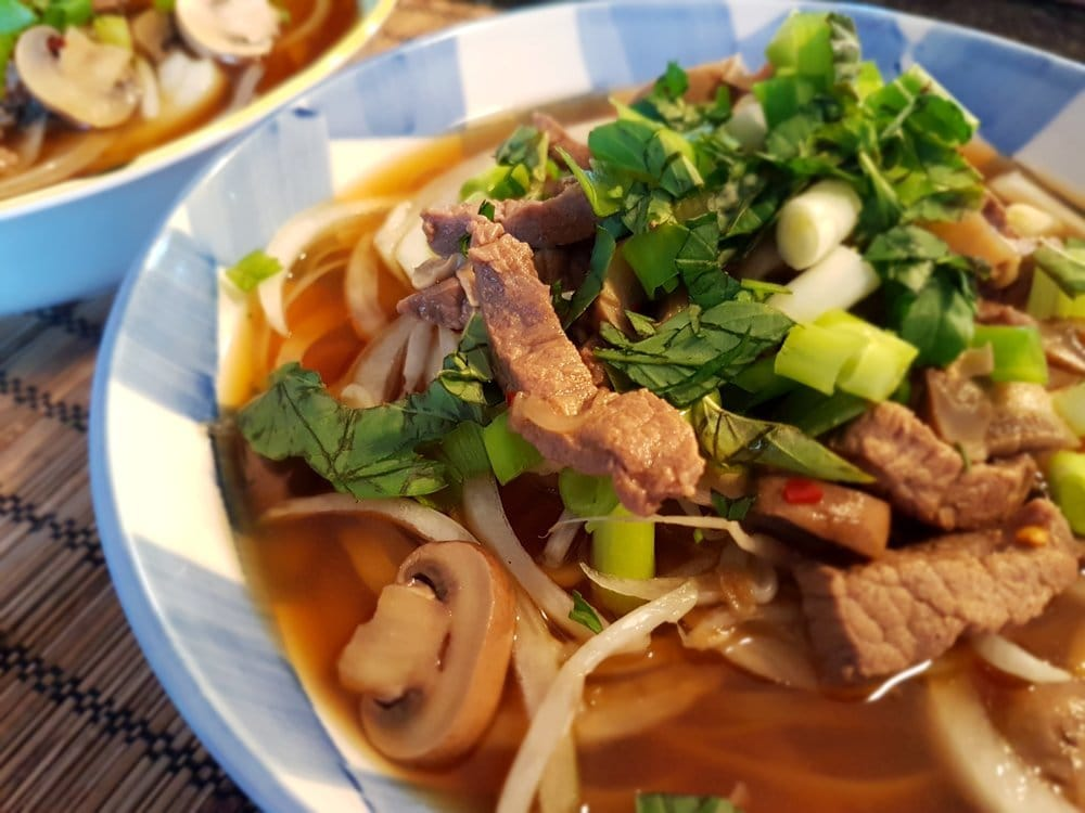 A hot bowl of Vietnamese Noodles with Beef and Mushrooms.