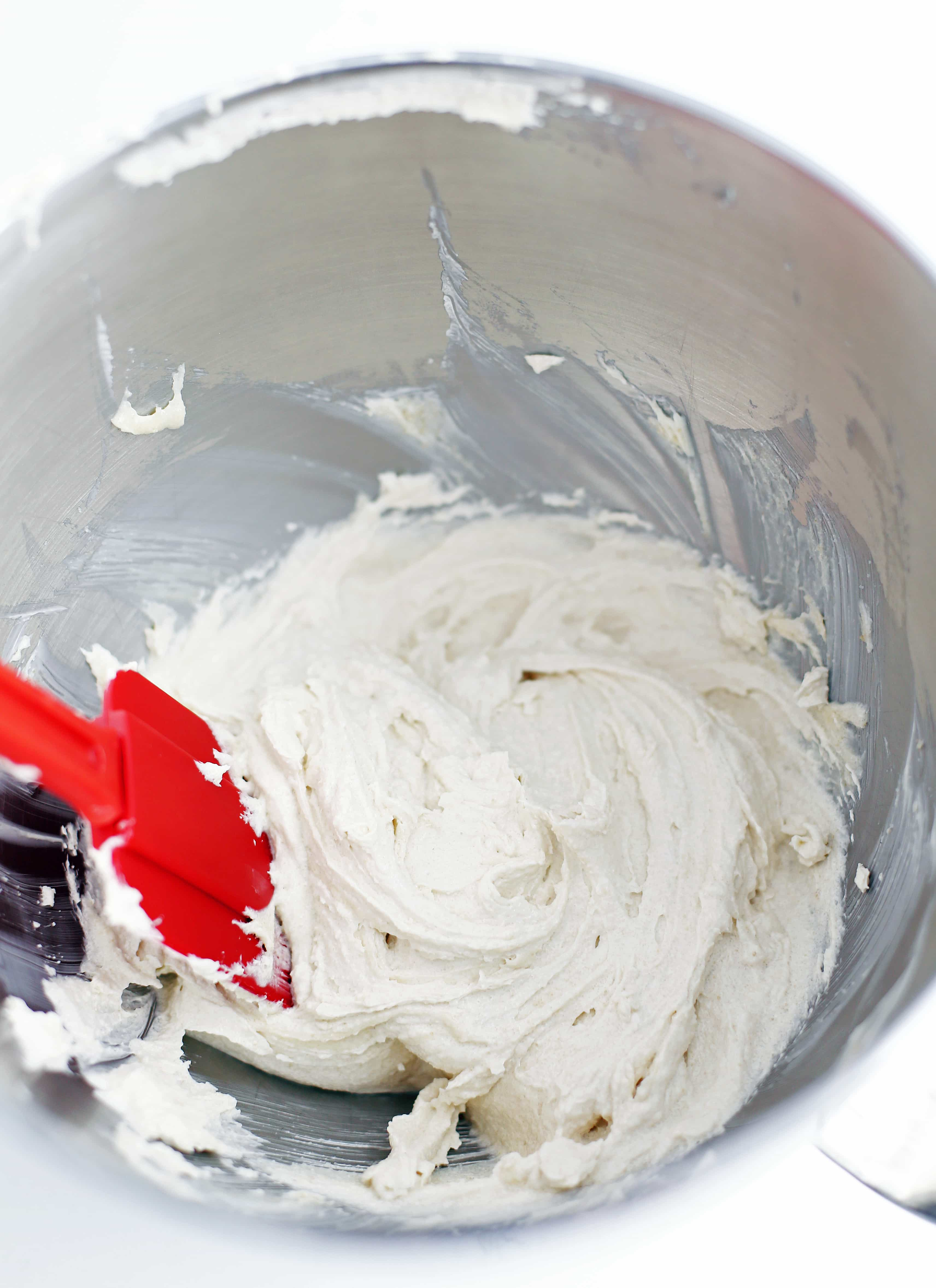Whipped butter and sugar in a stainless steel bowl.