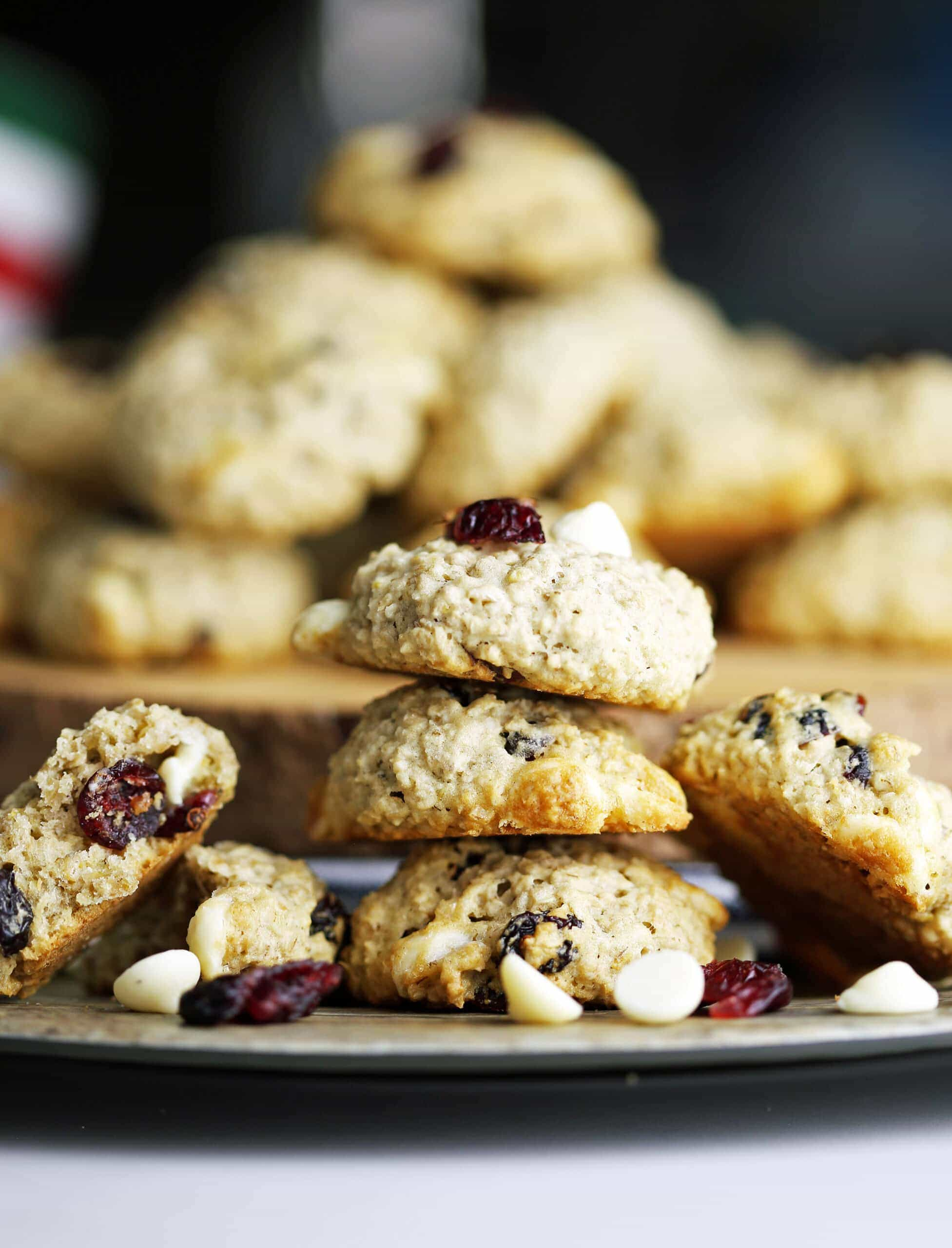 Three white chocolate cranberry oatmeal cookies on top of one another with more cookies piled high behind them.