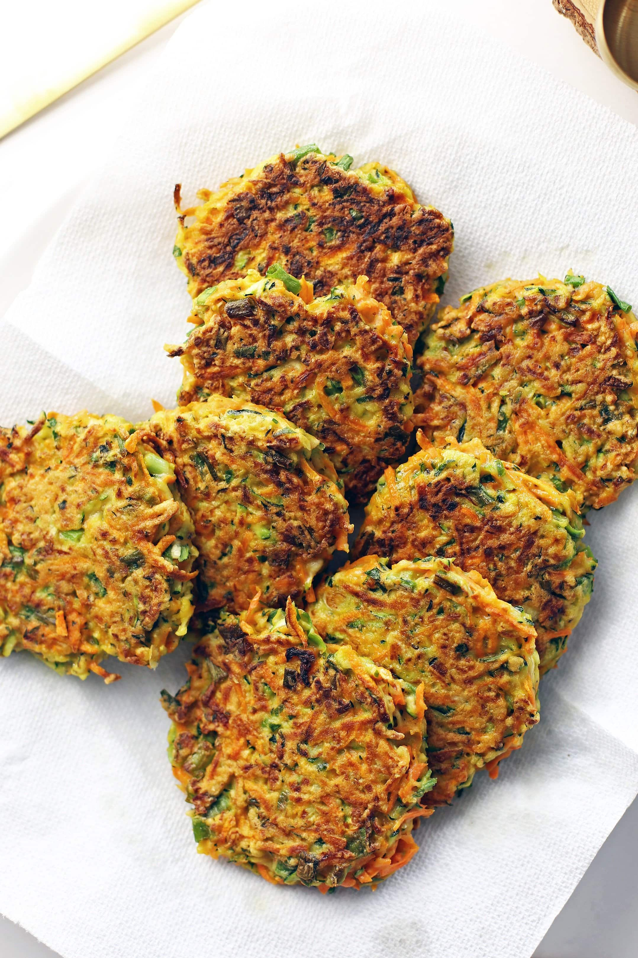 Eight freshly fried zucchini carrot pancakes placed on a paper towel lined plate.