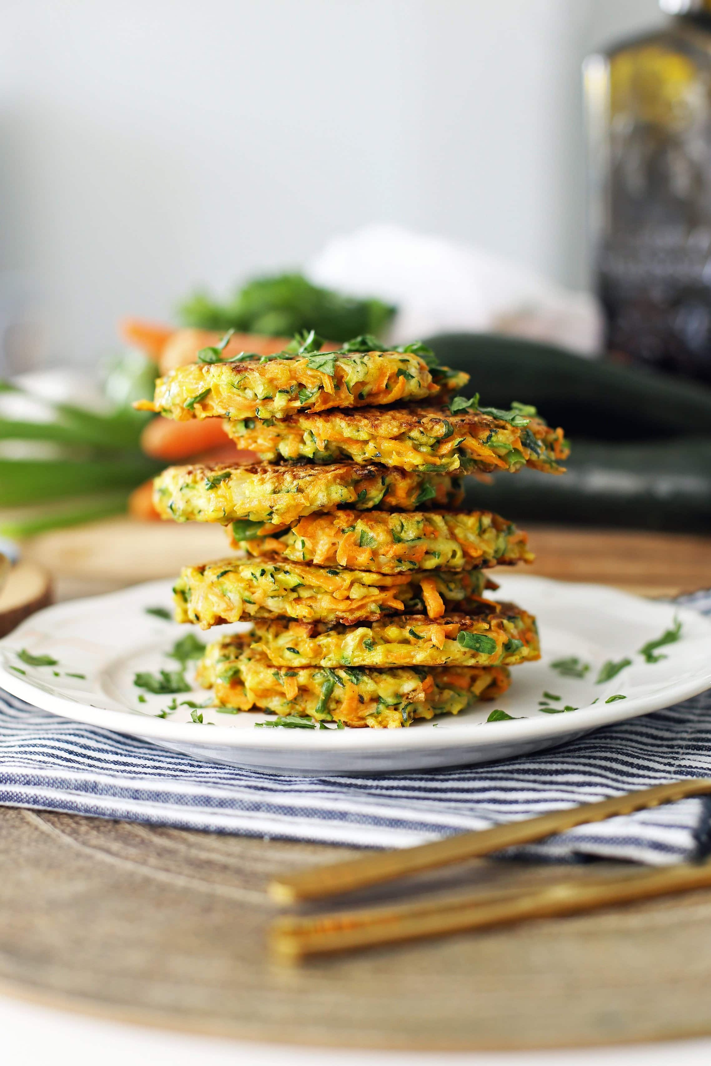 Seven zucchini carrot pancakes placed on top of one another and garnished with fresh parsley on a white plate.