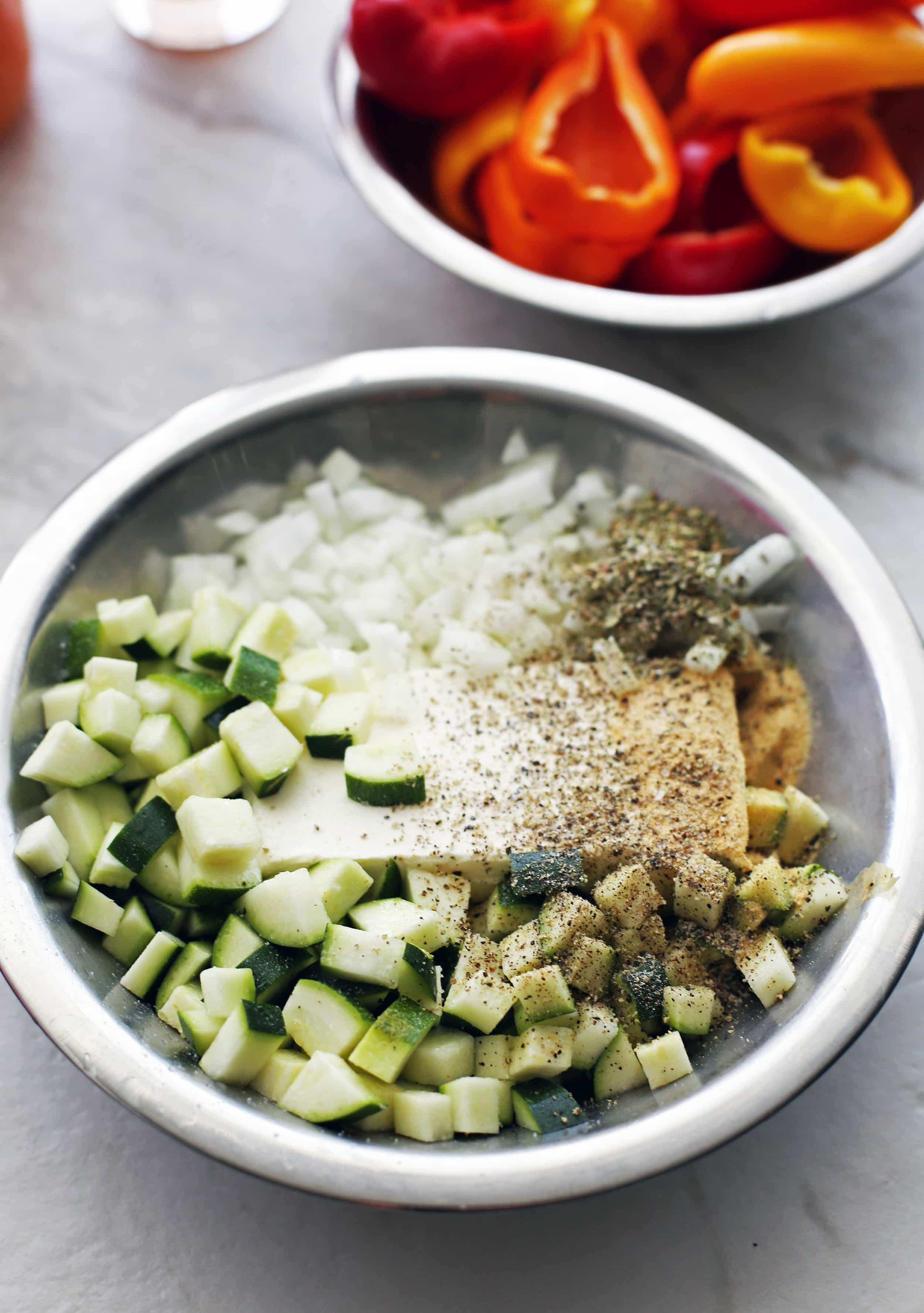 A metal bowl containing cream cheese, diced zucchini, onion, dried herbs, and spices.