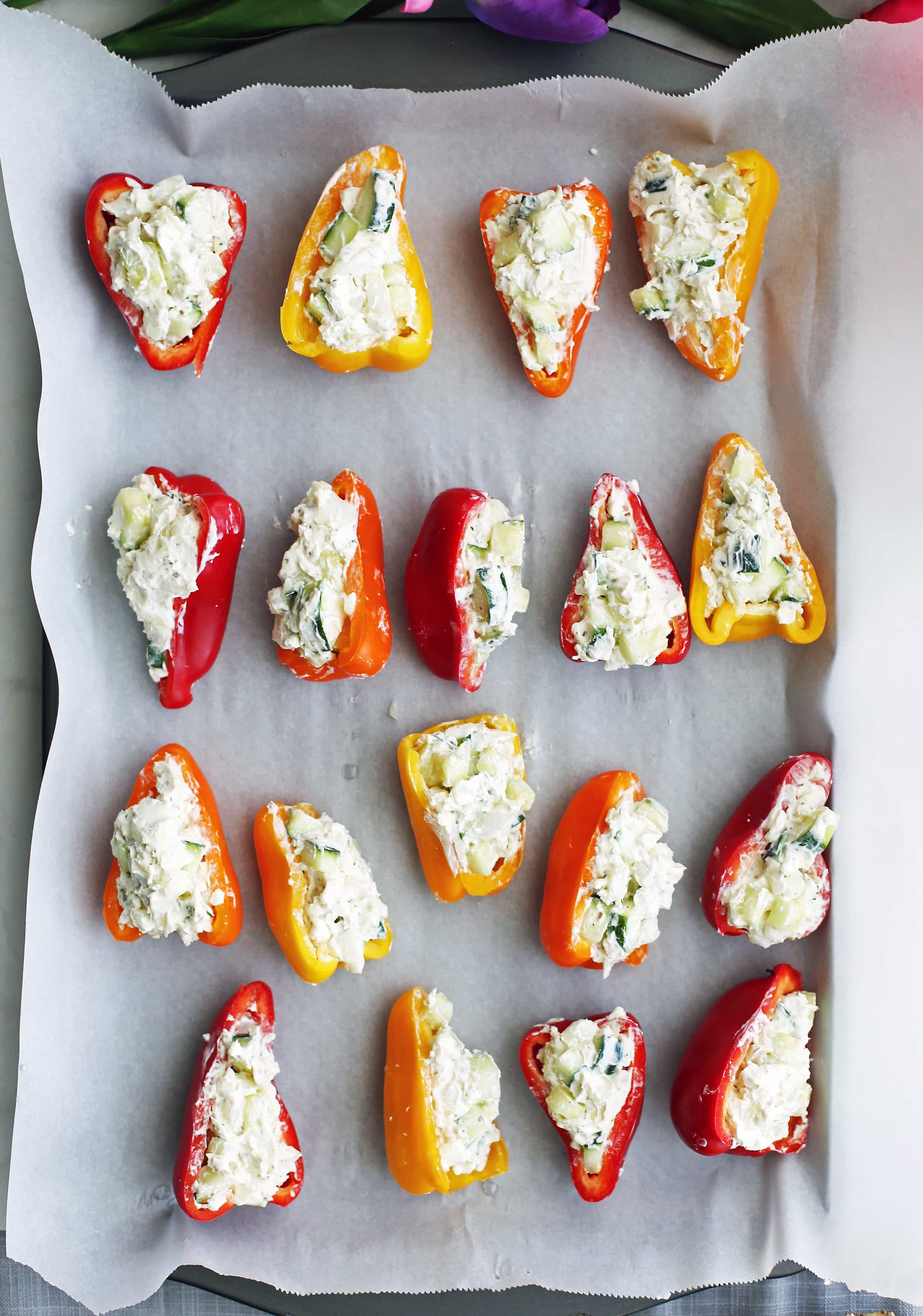 Zucchini and cream cheese mini stuffed peppers ready to be baked on a large baking sheet.